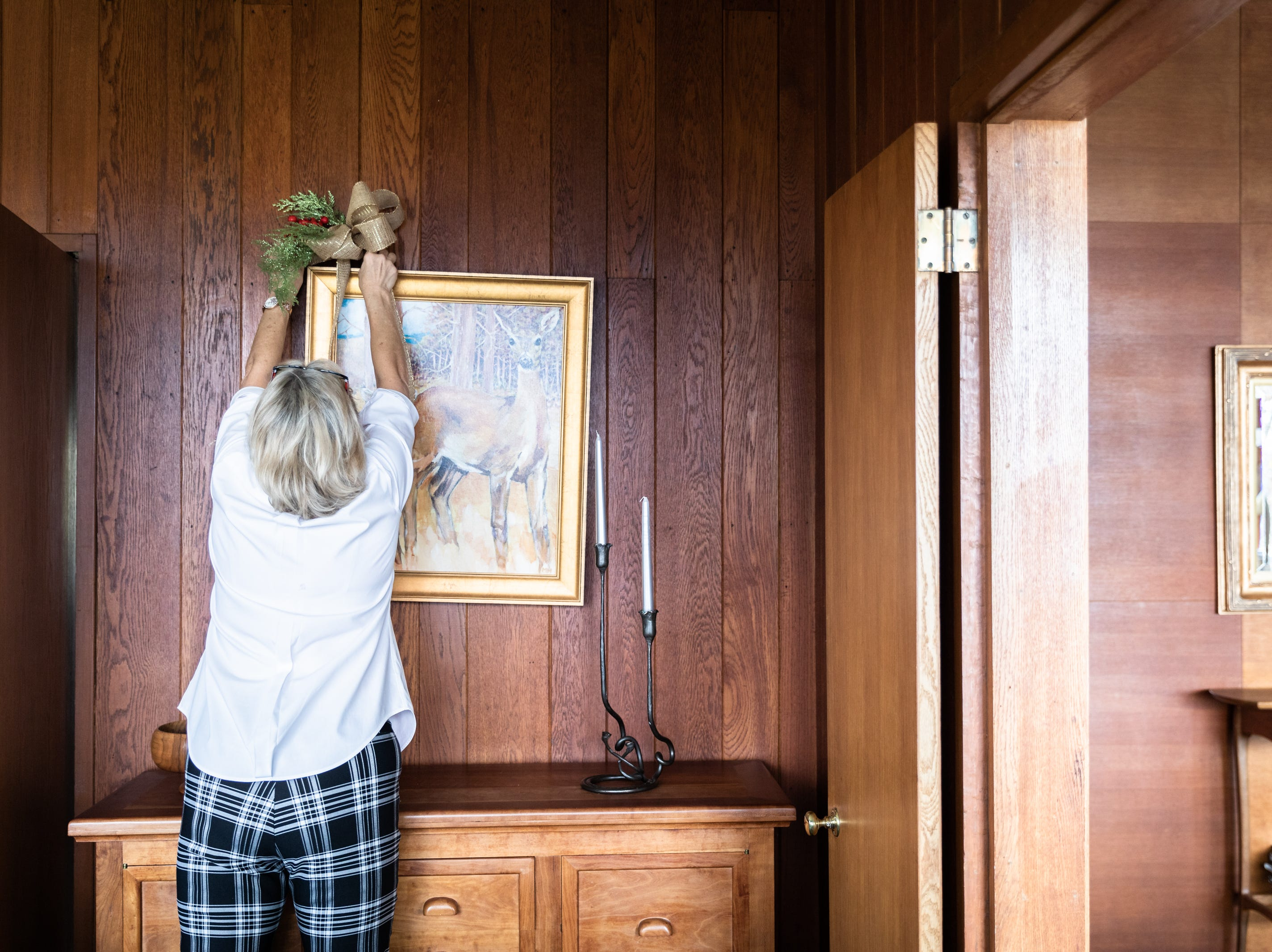 Kaye Myers, of Asheville, a member of the Governor's Western Residence Board of Directors, places a bow in the dining room of the residence on Patton Mountain Road in Asheville, Nov. 29, 2018.
