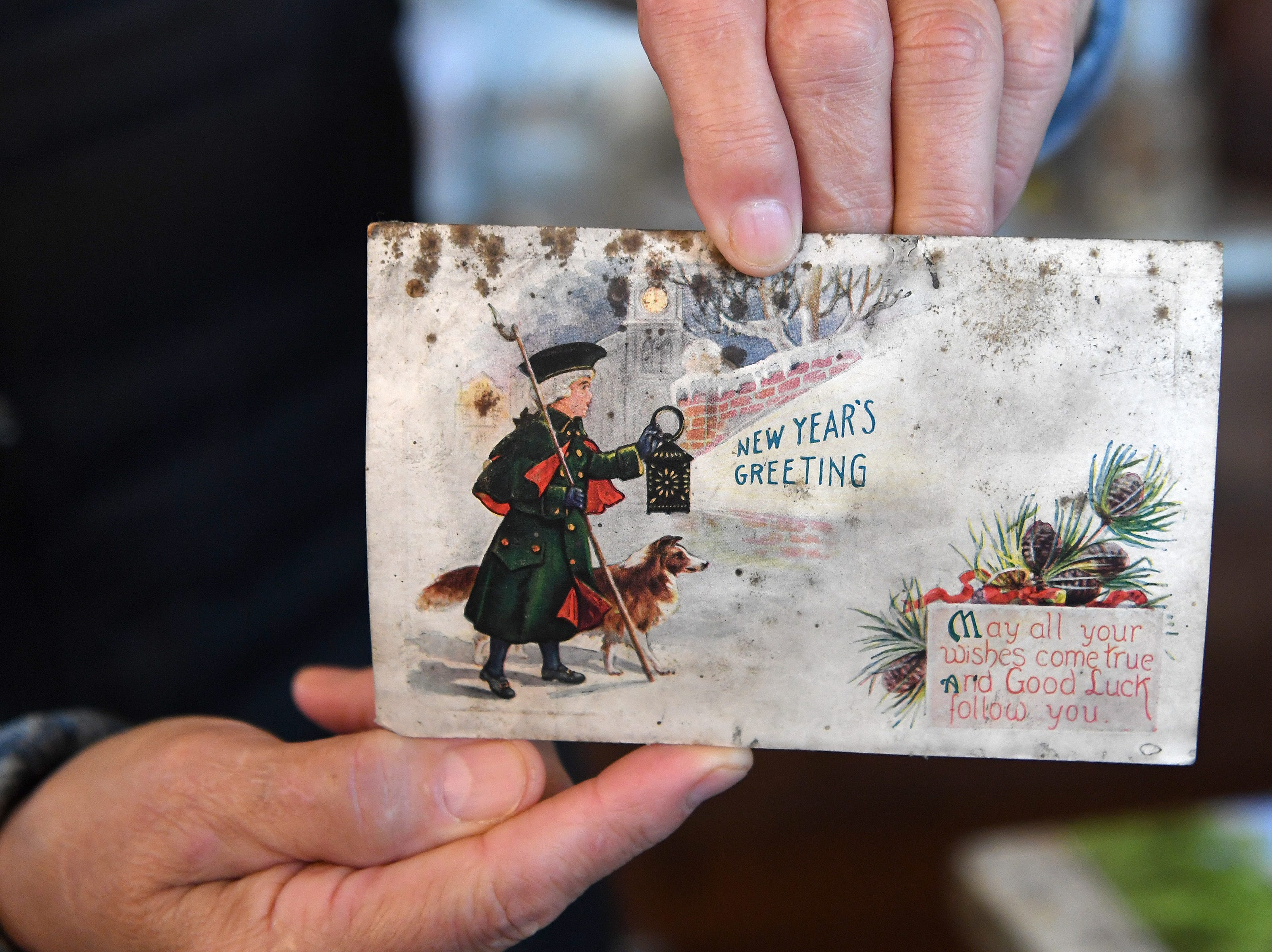 Linda Voorhees holds a New Year's postcard found in the garage when they remodeled their Montford home postmarked Jan. 1, 1923.