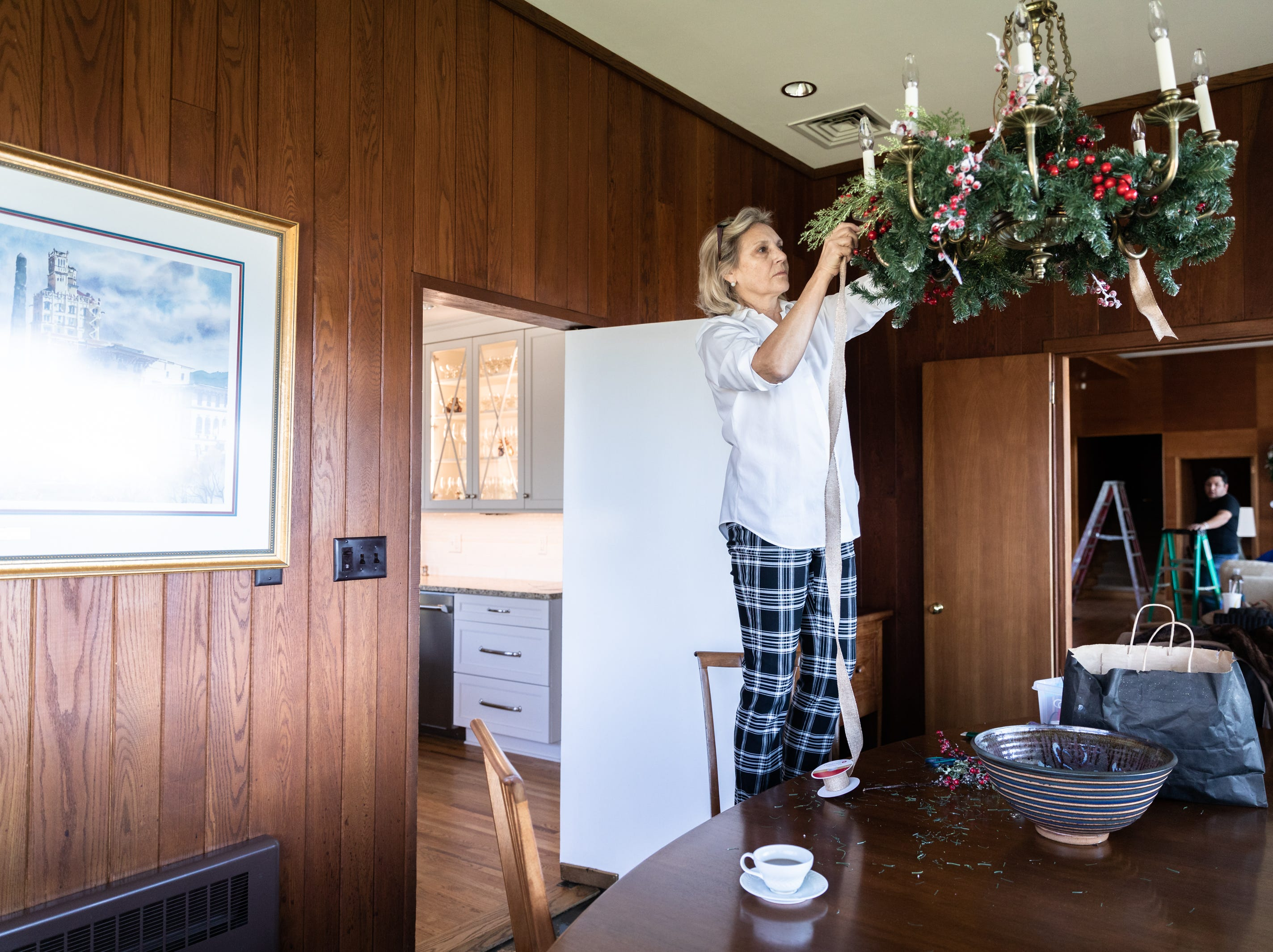 Kaye Myers, of Asheville, and a member of the Governor's Western Residence Board of Directors decorates the chandelier in the dining room in the residence on Patton Mountain Road in Asheville Nov. 29, 2018.