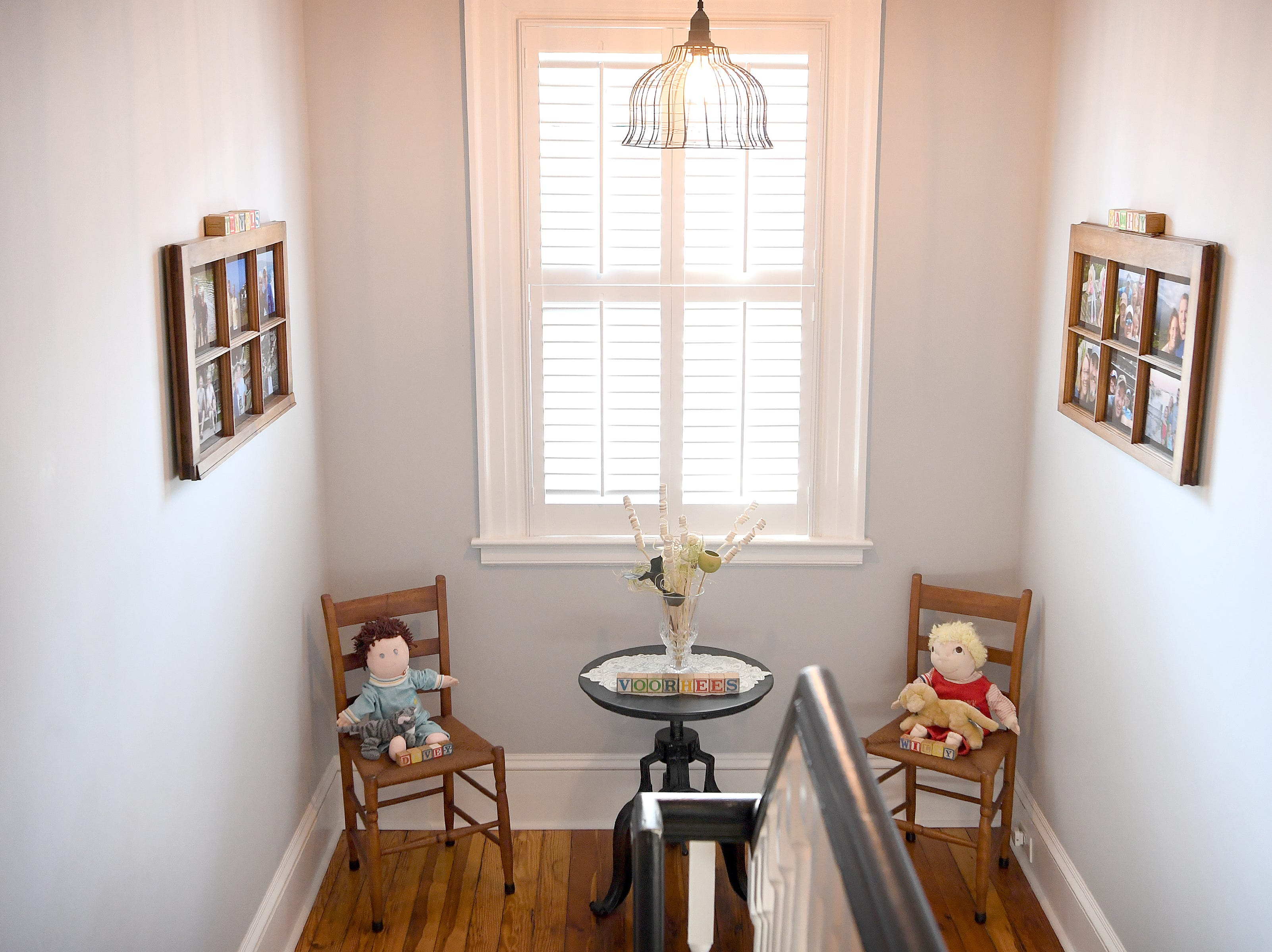 The first dolls owned by Linda and Marc Voorhees' children sit in antique chairs on a landing of the stairs leading to the second floor of their Montford home.