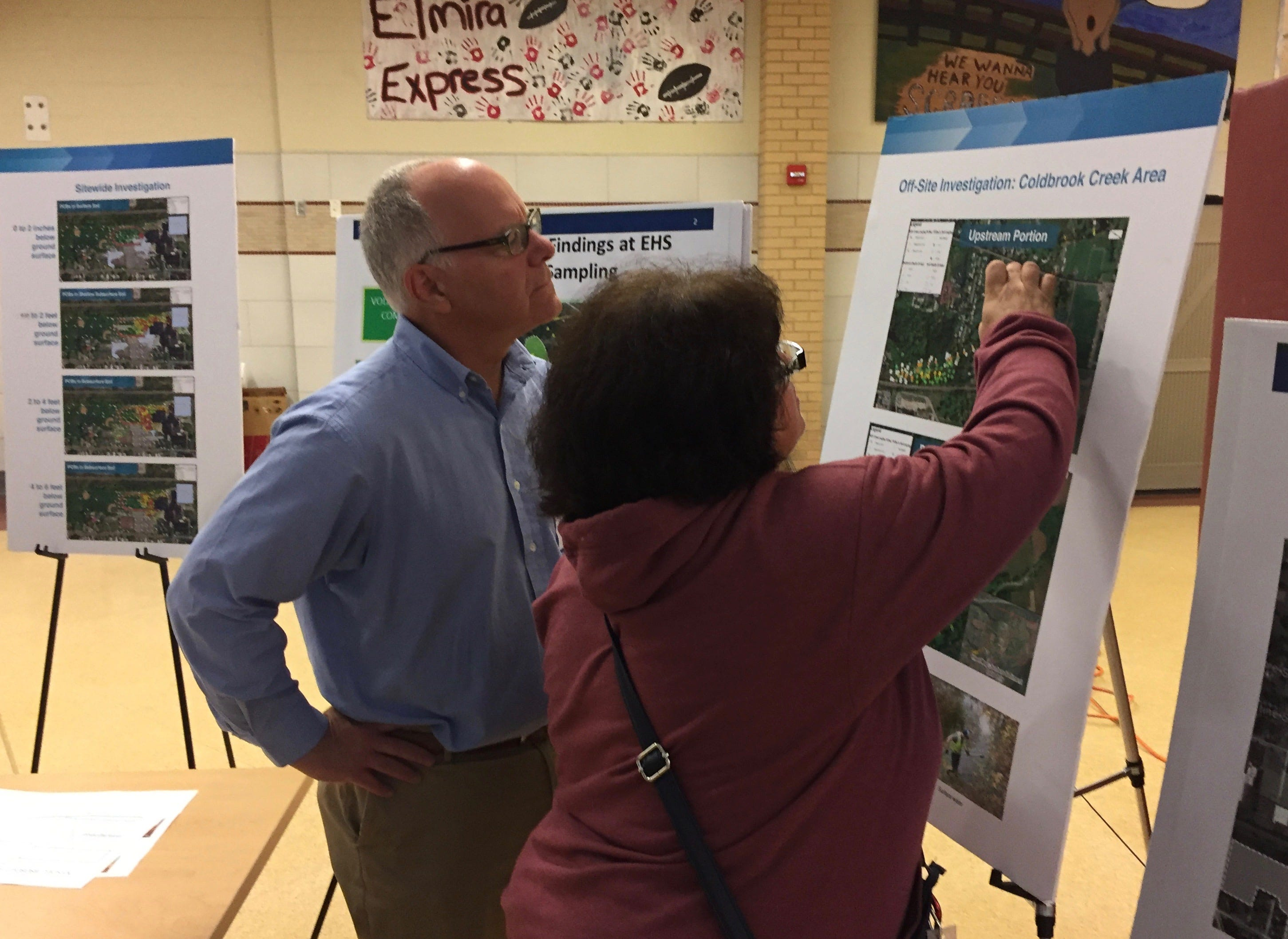 Elmira resident Amy Kuczka reviews a map with environmental consultant Paul Brookner at a public review of pollution held at Elmira High School in October.