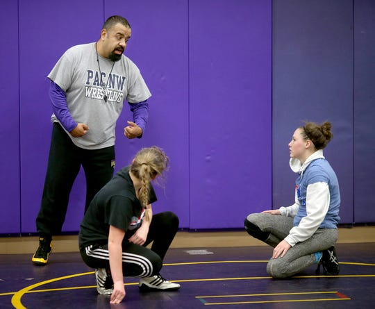 North Kitsap wrestling coach Robert Gomez works with junior Holly Beaudoin, right, during a recent practice.