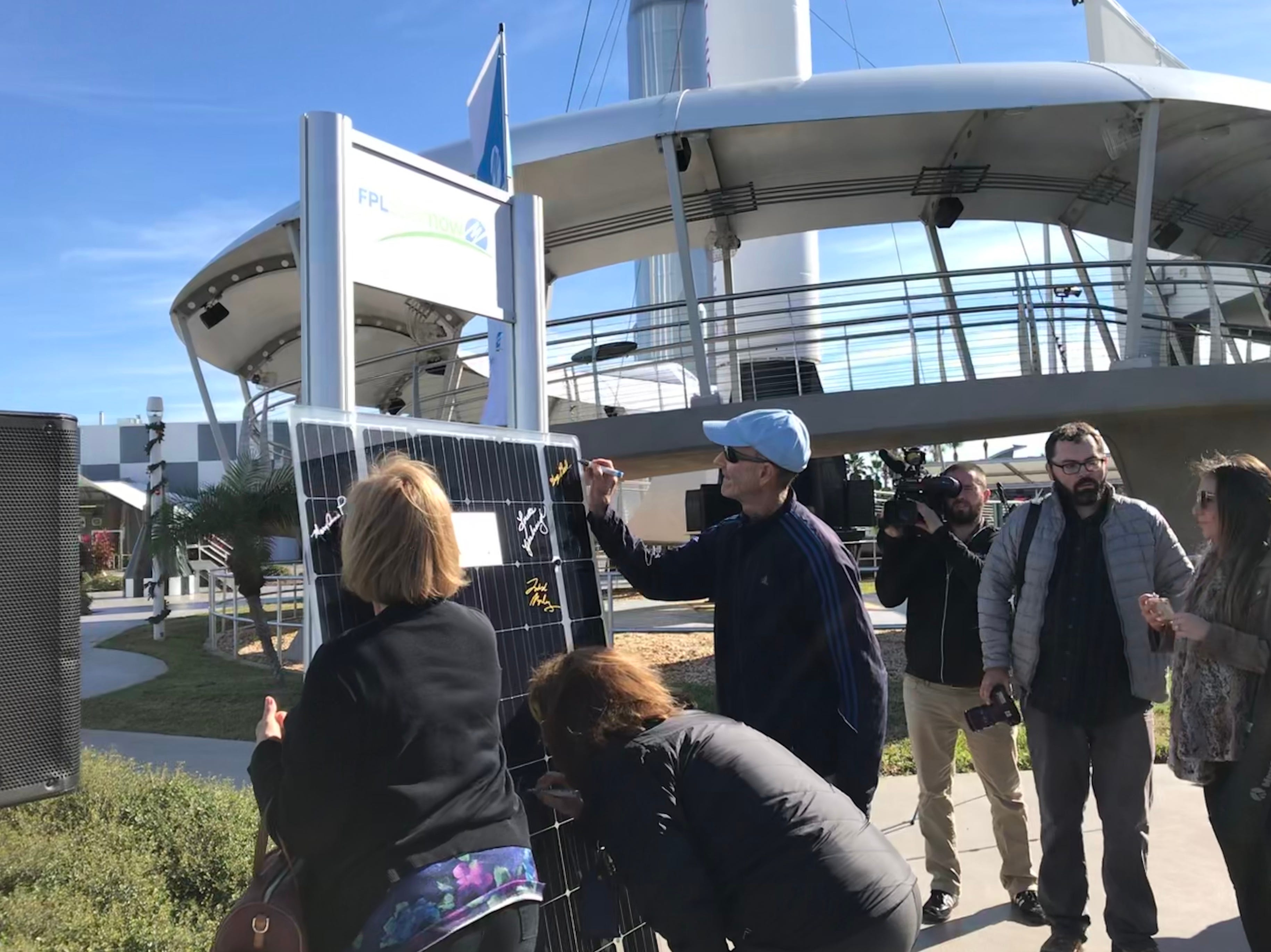 Florida Power & Light SolarNow participants sign a decorative solar panel at Kennedy Space Center Visitor Complex.
