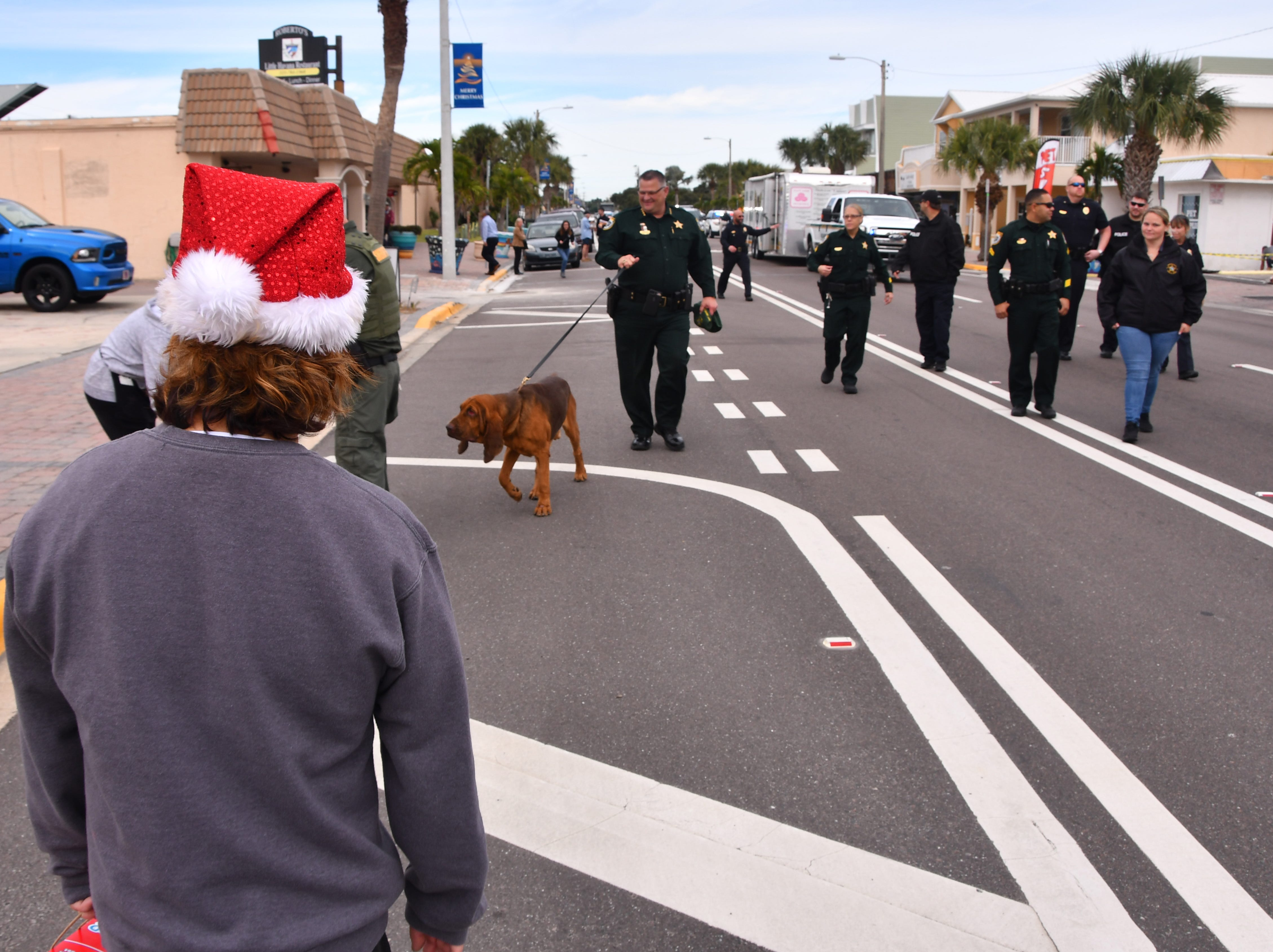 Brevard County Sheriff Wayne Ivey, Cocoa Beach Police Chief Scott  Rosenfeld and Deputy Police Chief Wes Mullins, along with other officers and deputies walked from 4th St. North  to Minutemen Causeway in Cocoa Beach collecting toys and pozing for photos. The Reverse Christmas Parade made its way through Brevard Thursday with stops in Titusville, Port St. John, Merritt Island, Cocoa Beach, Cocoa, Rockledge and Melbourne. Businesses and residents would bring unwrapped toys that were collected by the police and BCSO for needy children. People wait with toys on Orlando Ave. in Cocoa Beach.