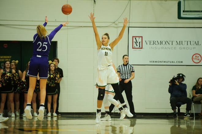 Vermont's Candice Wright (11) leaps to try to block the shot by Holy Cross' Lauren Manis (25) during the women's basketball game between the Holy Cross Crusaders and the Vermont Catamounts at Patrick Gym on Wednesday night November 28, 2018 in Burlington.