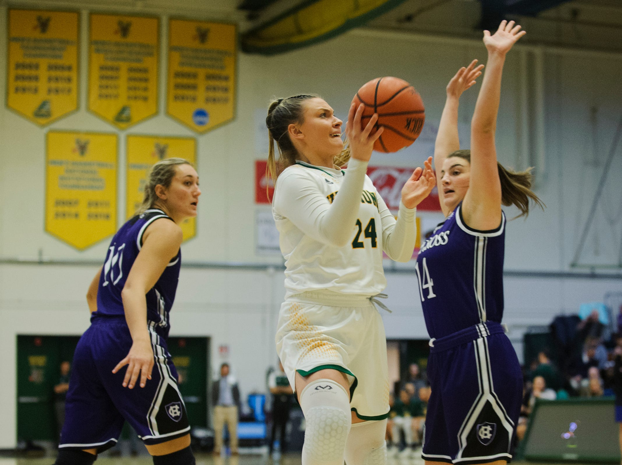 Vermont's Rose Caverly (24) leaps for a lay up during the women's basketball game between the Holy Cross Crusaders and the Vermont Catamounts at Patrick Gym on Wednesday night November 28, 2018 in Burlington.