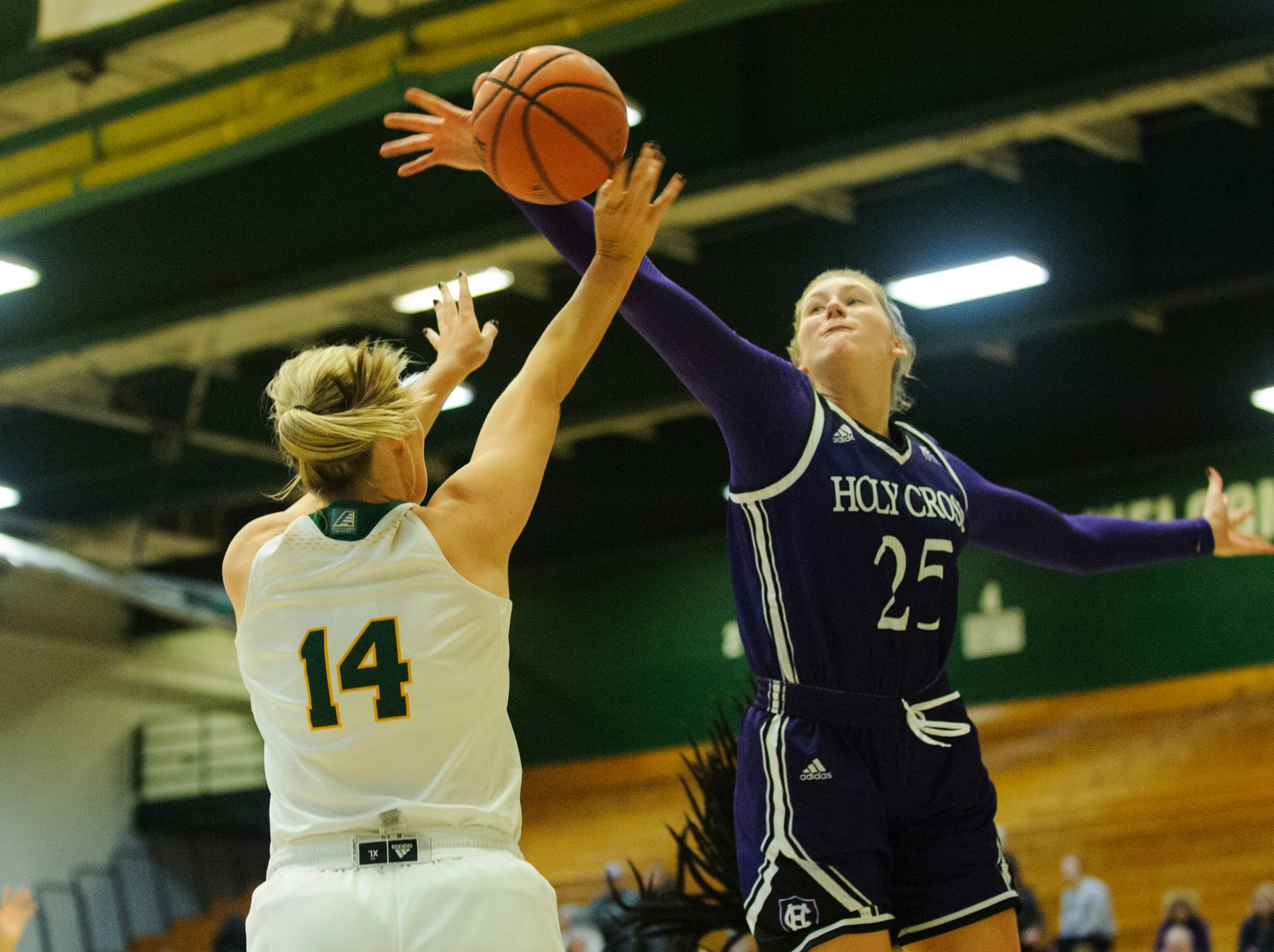 Holy Cross' Lauren Manis (25) blocks the shot by Vermont's Lauren Handy (14) during the women's basketball game between the Holy Cross Crusaders and the Vermont Catamounts at Patrick Gym on Wednesday night November 28, 2018 in Burlington.