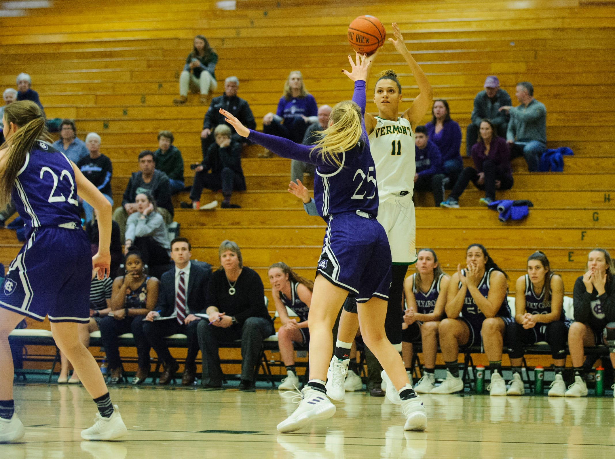 Vermont's Candice Wright (11) shoots a three pointer over Holy Cross' Lauren Manis (25) during the women's basketball game between the Holy Cross Crusaders and the Vermont Catamounts at Patrick Gym on Wednesday night November 28, 2018 in Burlington.