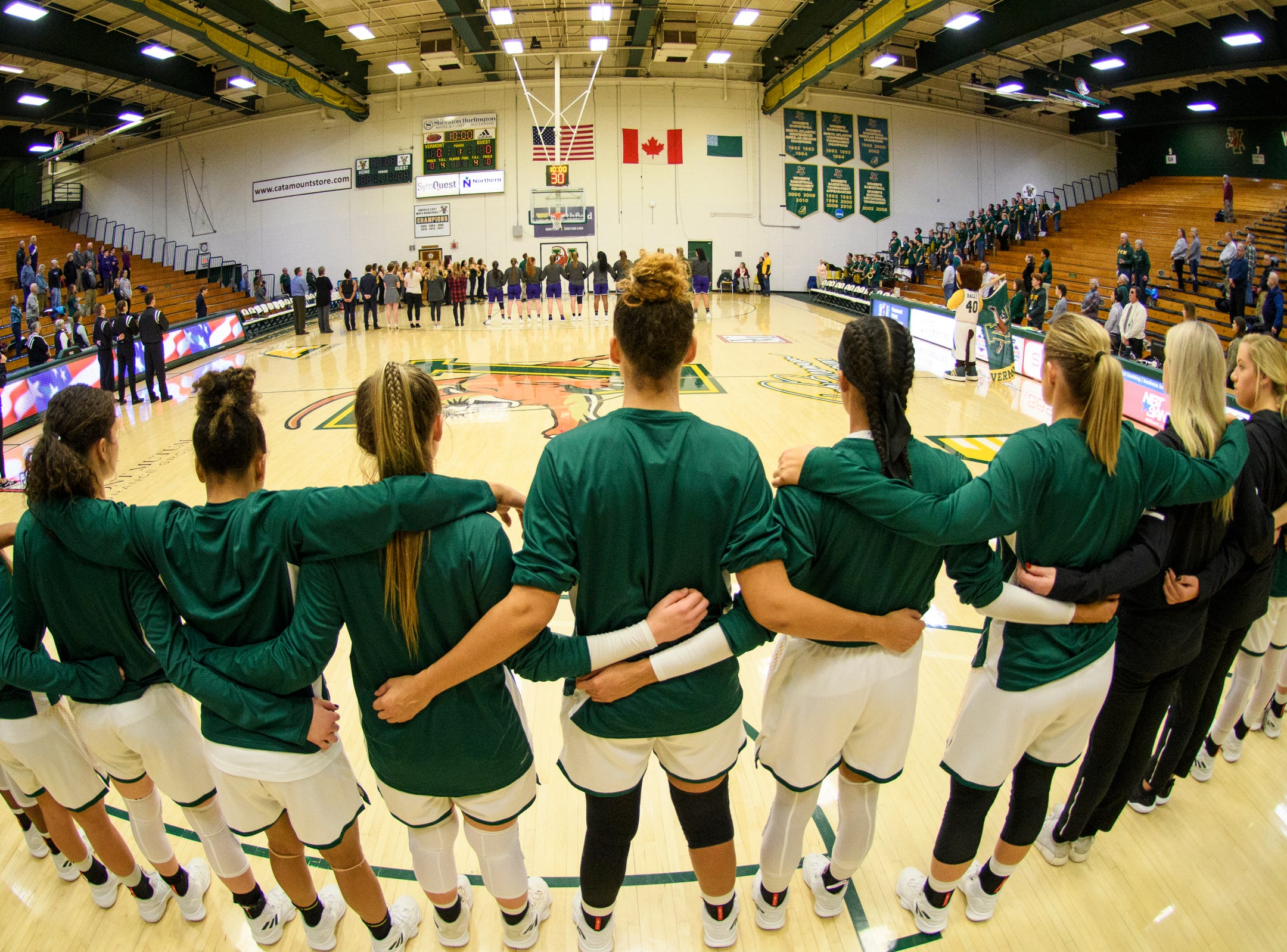 The teams listen to the National Anthem during the women's basketball game between the Holy Cross Crusaders and the Vermont Catamounts at Patrick Gym on Wednesday night November 28, 2018 in Burlington.