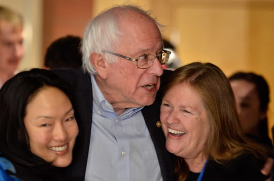"Sen. Bernie Sanders, center, and his wife Jane O'Meara Sanders, right, pose for a photo with supporter Jane Kim of the San Francisco Board of Supervisors at the opening night of The Sanders Institute Gathering event at ECHO Leahy Center for Lake Champlain on Nov. 29, 2018. The Gathering is billed as a meeting of  ""250 leading progressive minds to envision – and to actualize – a better future for our country and the world,' organized by the institute co-founded by  Jane O'Meara Sanders."