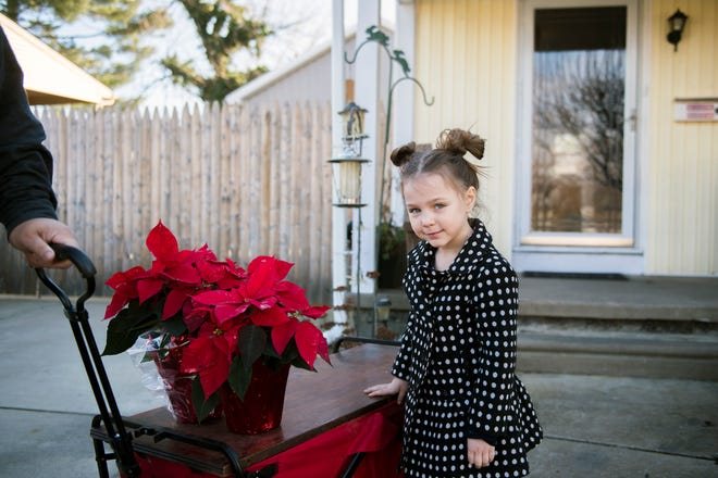 Lilly Parker, 5, poses next to her wagon Thursday, Nov. 29, 2018 in Stratford, N.J. Lilly delivers poinsettias to neighbor's doorsteps accompanied with a card she signs for the holiday season.