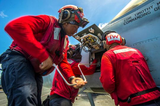 Sailors work on the gun panel on an F/A-18E Super Hornet aircraft aboard the USS Ronald Reagan in August.
