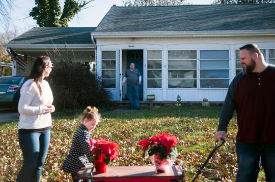 Neighbor John Barrett praises five-year-old Lilly Parker, center, for poinsettias he received from her Thursday, Nov. 29, 2018 in Stratford, N.J.