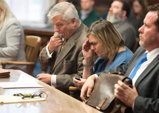 Angela Wagner, 48, of South Webster, puts on her reading glasses as she follows along with the 22 counts of her indictment at the Pike County Courthouse during her arraignment on Thursday, November 29, 2018 in Waverly, Ohio.
