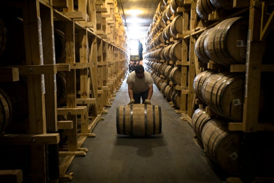 An employee of Buffalo Trace rolls a barrel of bourbon to be bottled at Buffalo Trace Distillery in Frankfort, Ky., on Wednesday, Nov. 28, 2018.