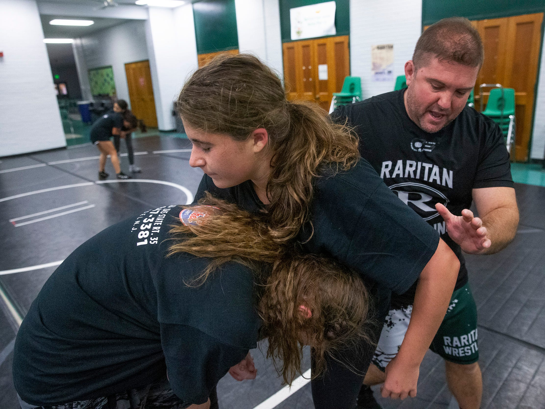 Coach Robert Nucci works with Victoria Hurt and Brook Gaetani on takedown moves. NJSIAA is offering wrestling for girls this year and they will participate in an all girls tournament at the end of the season. Raritan High School Wrestling is fielding nearly a  full girls team this year. While girls mostly practice separately from the boys, they are in a room next to the boys and frequent coaching sessions happen in the boys room to teach moves.