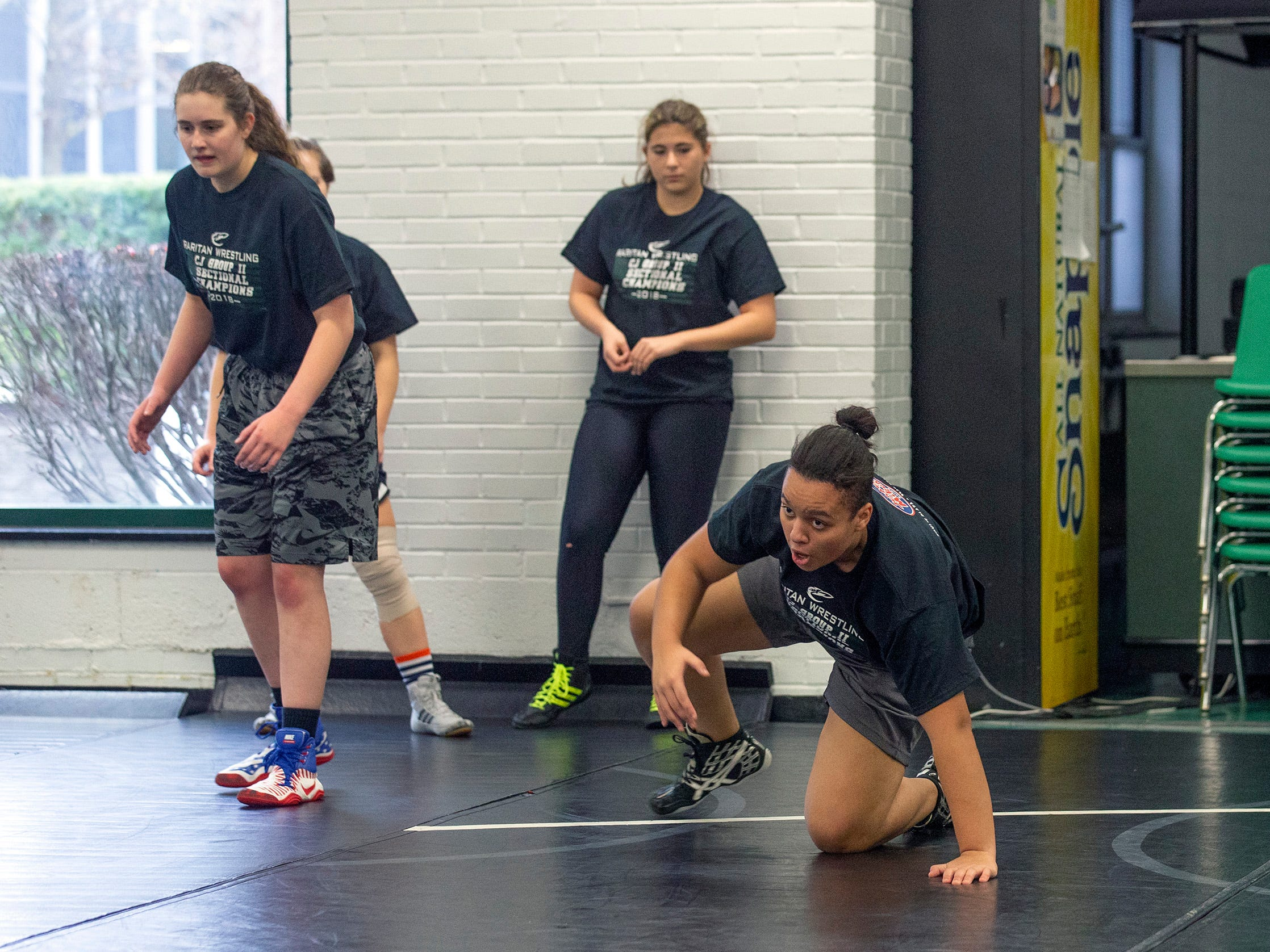 Mia Lazaurs  and others work on drills. NJSIAA is offering wrestling for girls this year and they will participate in an all girls tournament at the end of the season. Raritan High School Wrestling is fielding nearly a  full girls team this year. While girls mostly practice separately from the boys, they are in a room next to the boys and frequent coaching sessions happen in the boys room to teach moves.