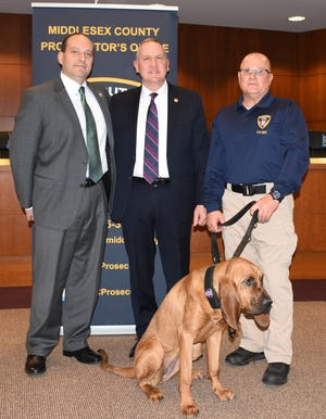 Middlesex County Prosecutor Andrew Carey, Middlesex County Prosecuto'rs Office Deputy Chief Christopher Penna and Canine Handler Michael Campbell, holding Beckett, Bloodhound who has joined the Middlesex County Canine Search and Rescue Team.
