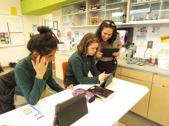 Aayushi Singh of Edison and Hannah Malko of Clark show their work to Dr. Corinna Crafton, Middle School Head.