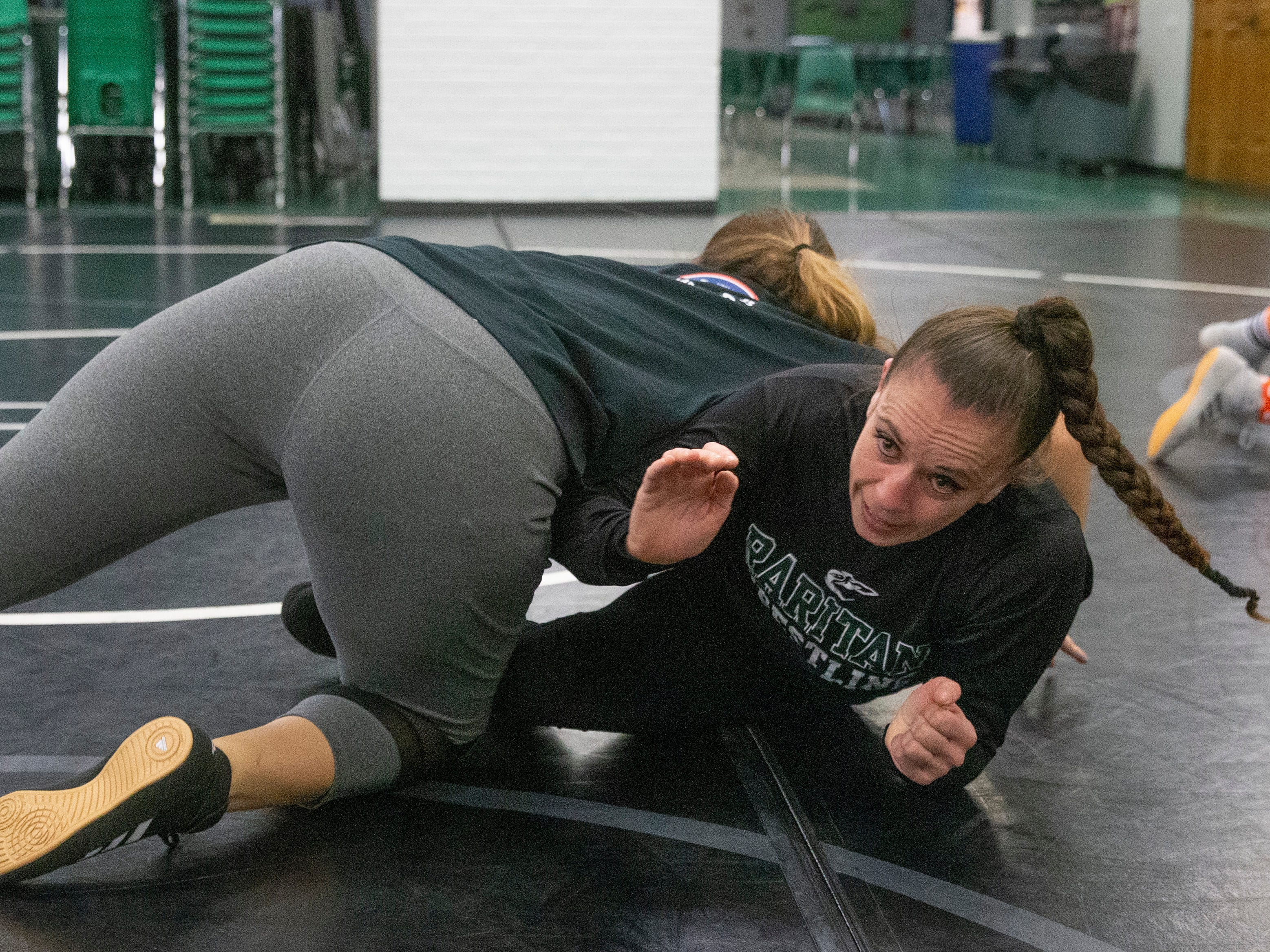 Girls Wrestling Coach Melissa Gardner works with one of the girls on moves. NJSIAA is offering wrestling for girls this year and they will participate in an all girls tournament at the end of the season. Raritan High School Wrestling is fielding nearly a  full girls team this year. While girls mostly practice separately from the boys, they are in a room next to the boys and frequent coaching sessions happen in the boys room to teach moves.