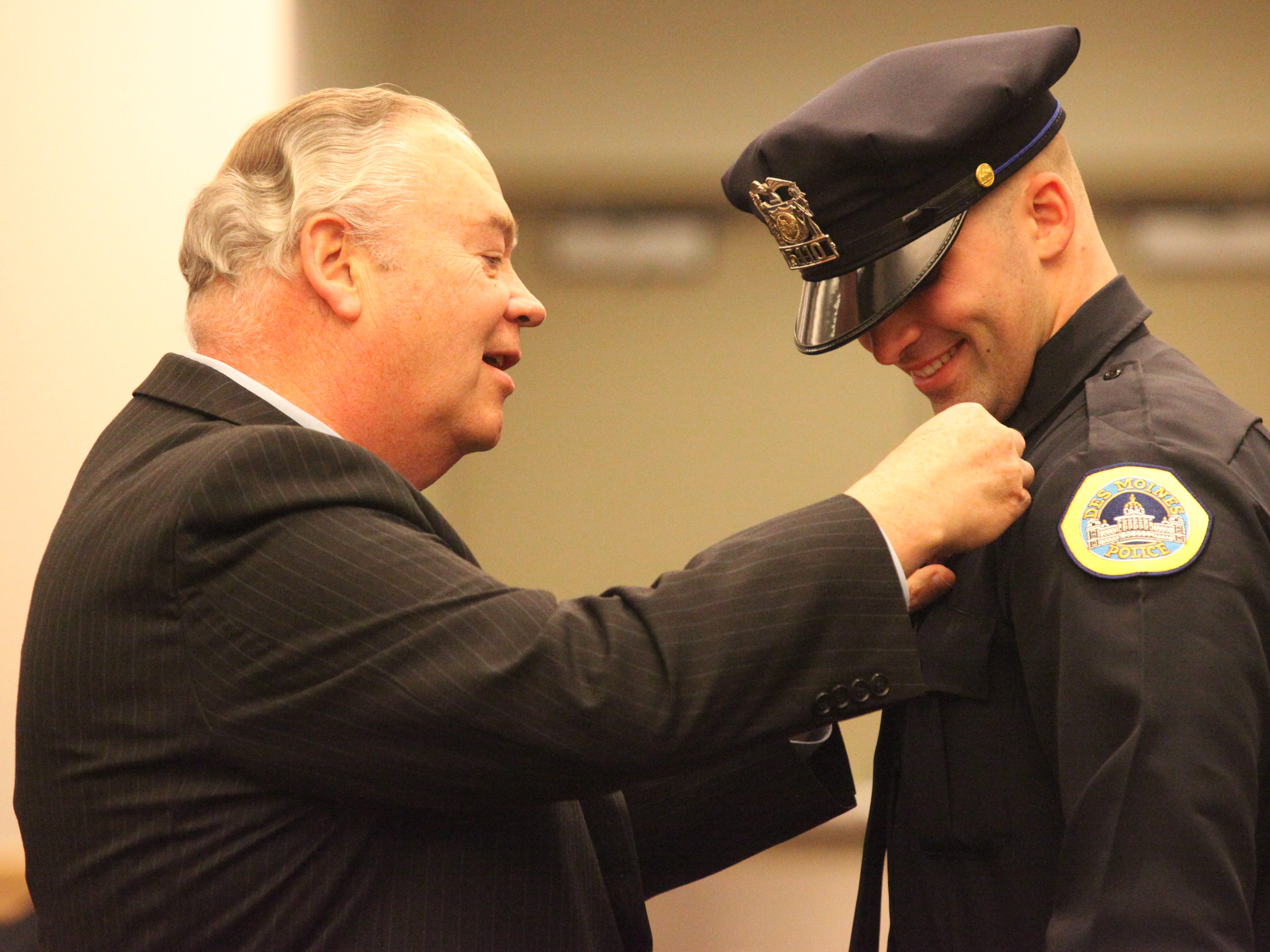 Bill McCarthy pins a badge on his nephew, Benjamin McCarthy, on March 18, 2011 at the Iowa Event Center in Des Moines. Des Moines Police Department held a graduation ceremony for 14 recruit officers. These officers  participated in a 22-week training program as part of the 70th recruit class at the Des Moines Regional Police Academy. (Andrea Melendez/The Register)