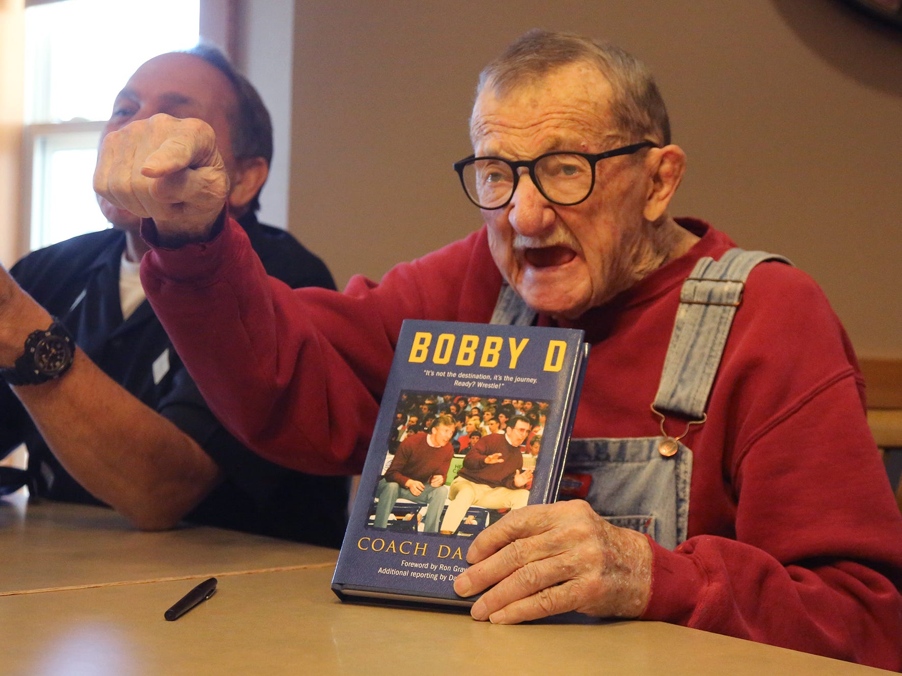 "Legendary wrestling coach Bob Darrah tells a story while holding a copy of the book ""Bobby D: Coach Darrah"" by Dan McCool during a book signing at Windsor Manner in Indianola on Feb. 4, 2018."