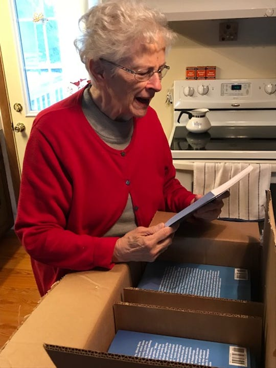 Marjorie Marie Thompson opens a book of poems written by her son