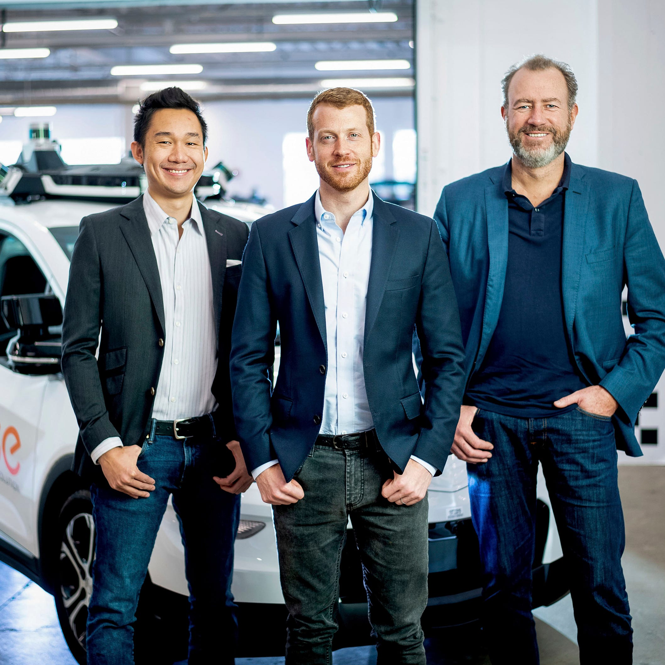 Cruise Automation's Dan Kan and Kyle Vogt pose for a photo with General Motors' Dan Ammann at Cruise Automation offices in San Francisco, Calif. on Nov. 20, 2018.