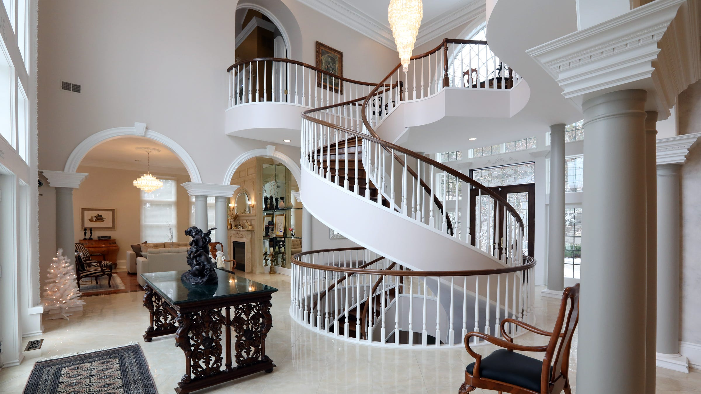 The elegant staircase is the focal point on three floors, from the curving second floor loft to the finely finished lower level in this house in Clarkston. Around it the floor plan is wide open.