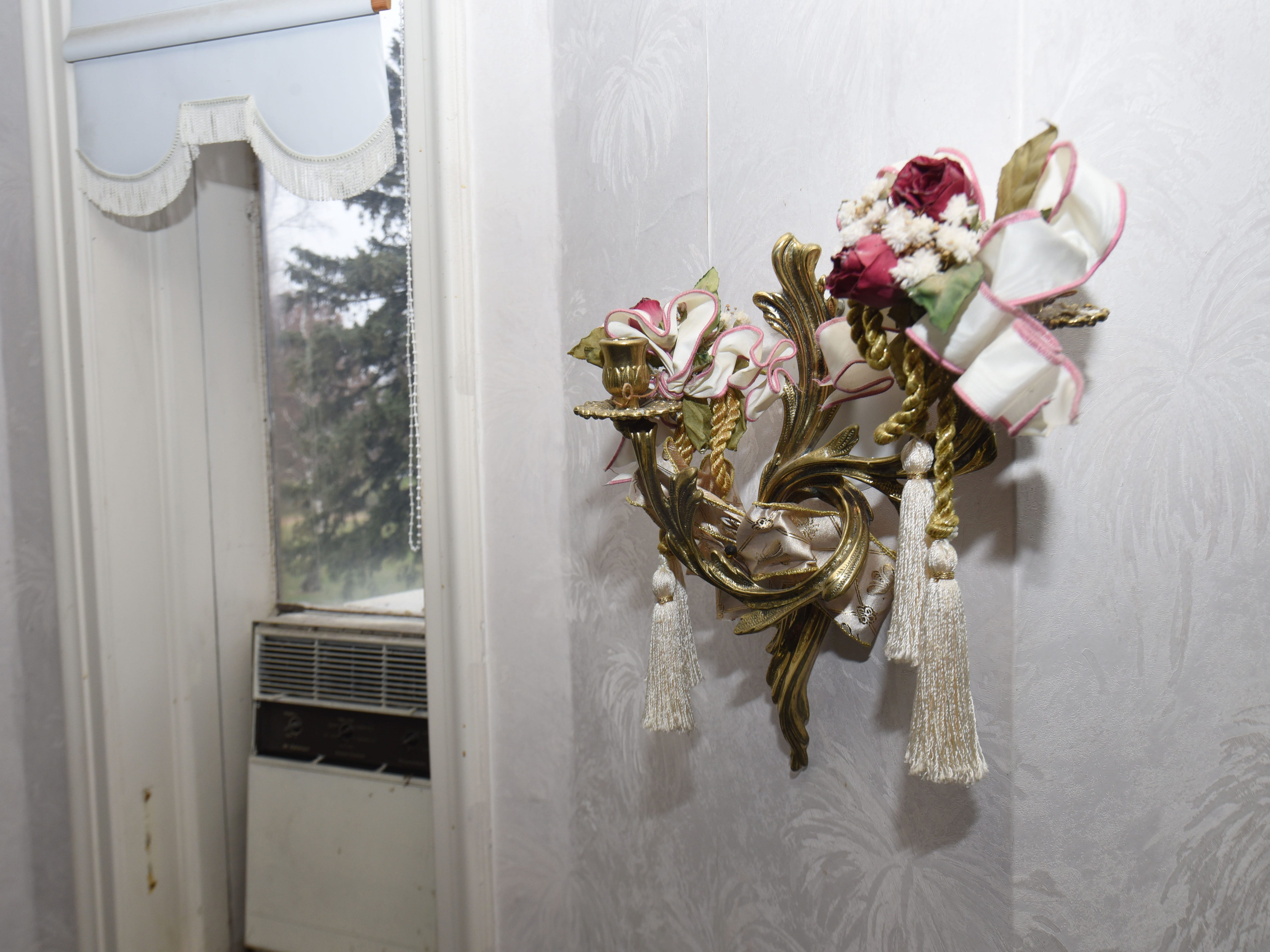 Ribbons, flowers and tassels adorn a sconce.