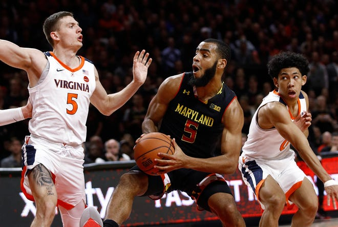 Maryland guard Eric Ayala, center, drives the ball as he is pressured by Virginia guards Kyle Guy, left, and Kihei Clark during the second half.