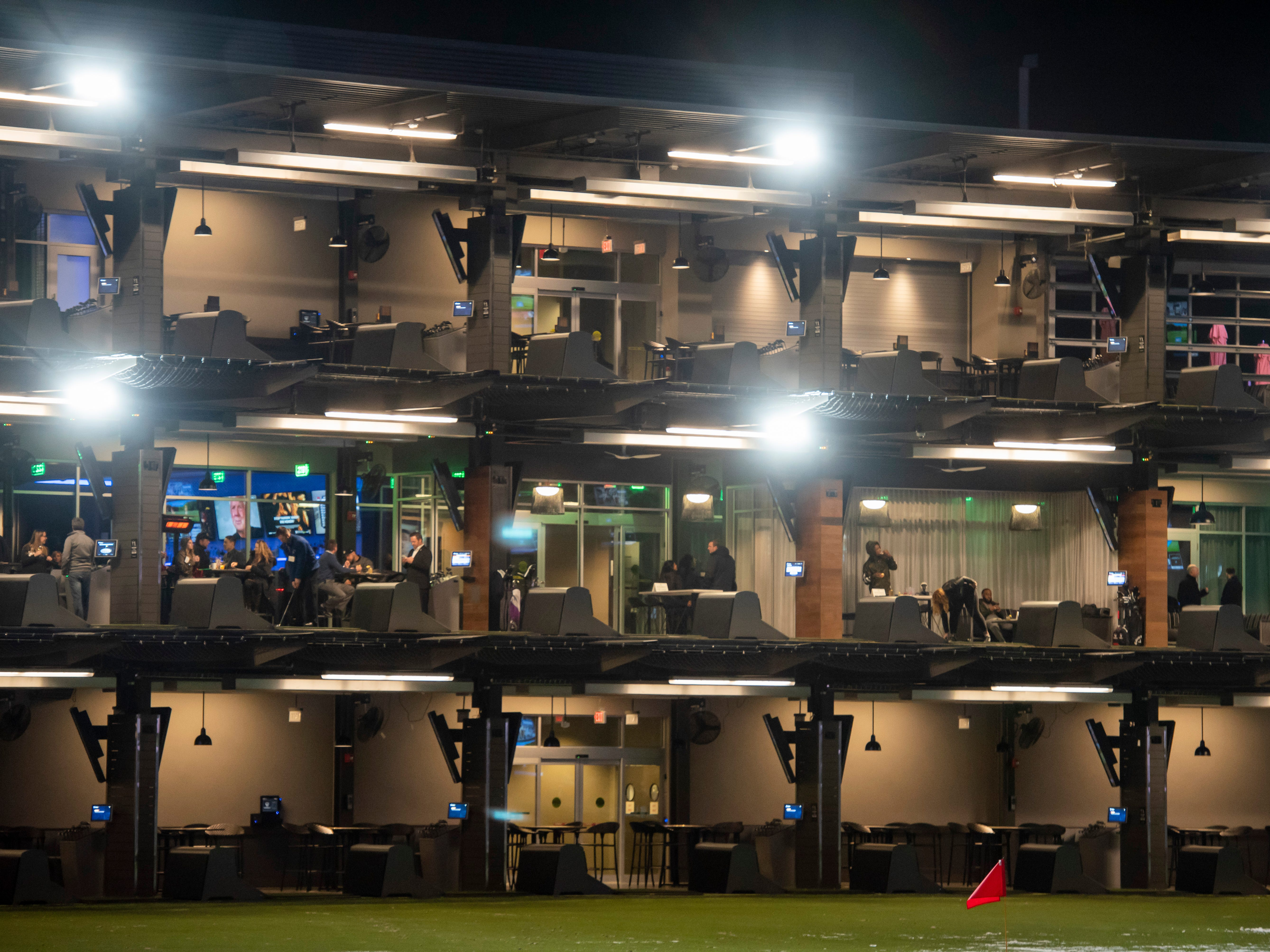 Guests try out one of the heated driving ranges during a preview event at Topgolf, in Auburn Hills.