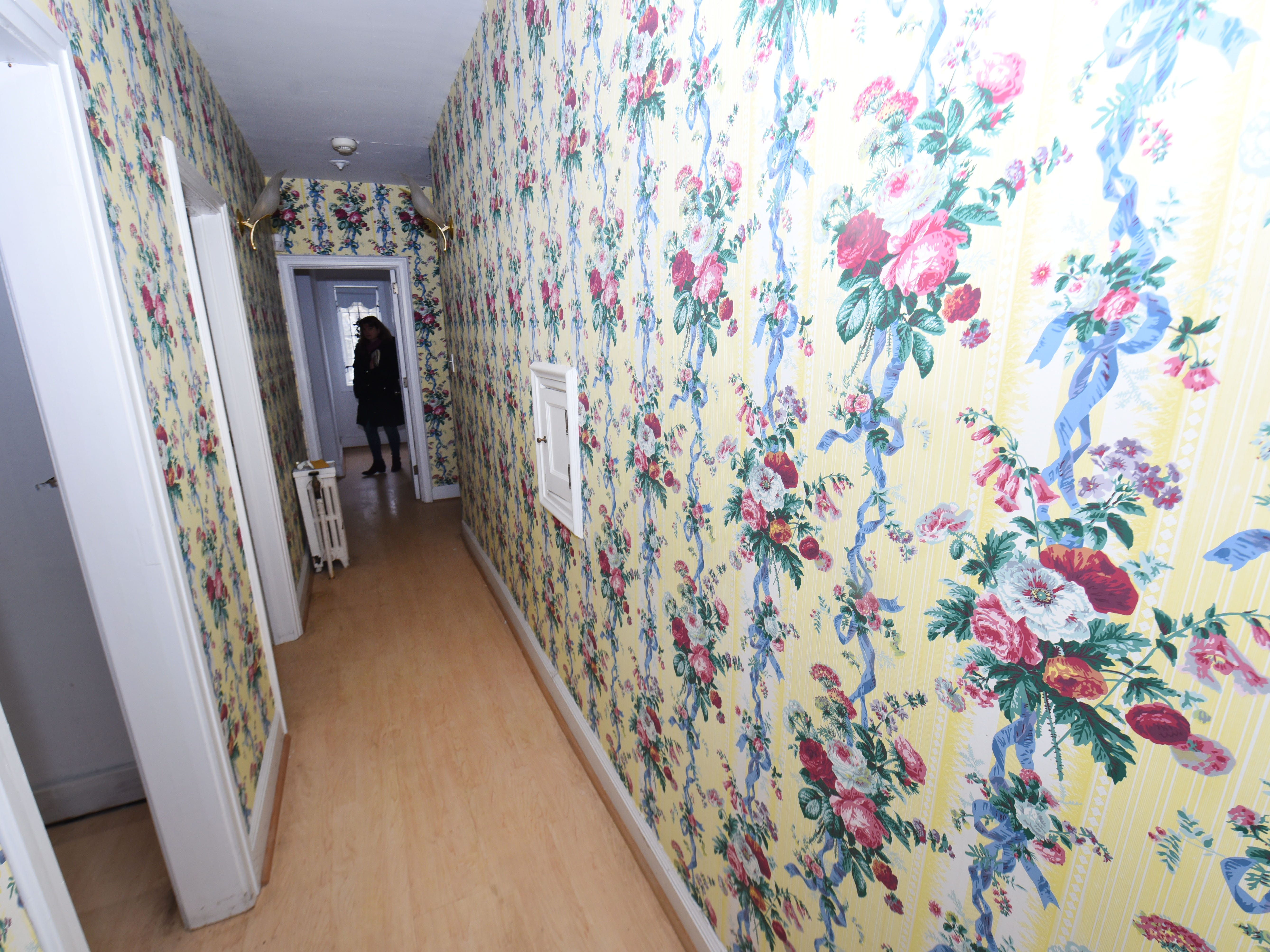 The hallway outside the bedroom of Aretha Franklin is covered in rose wallpaper design.