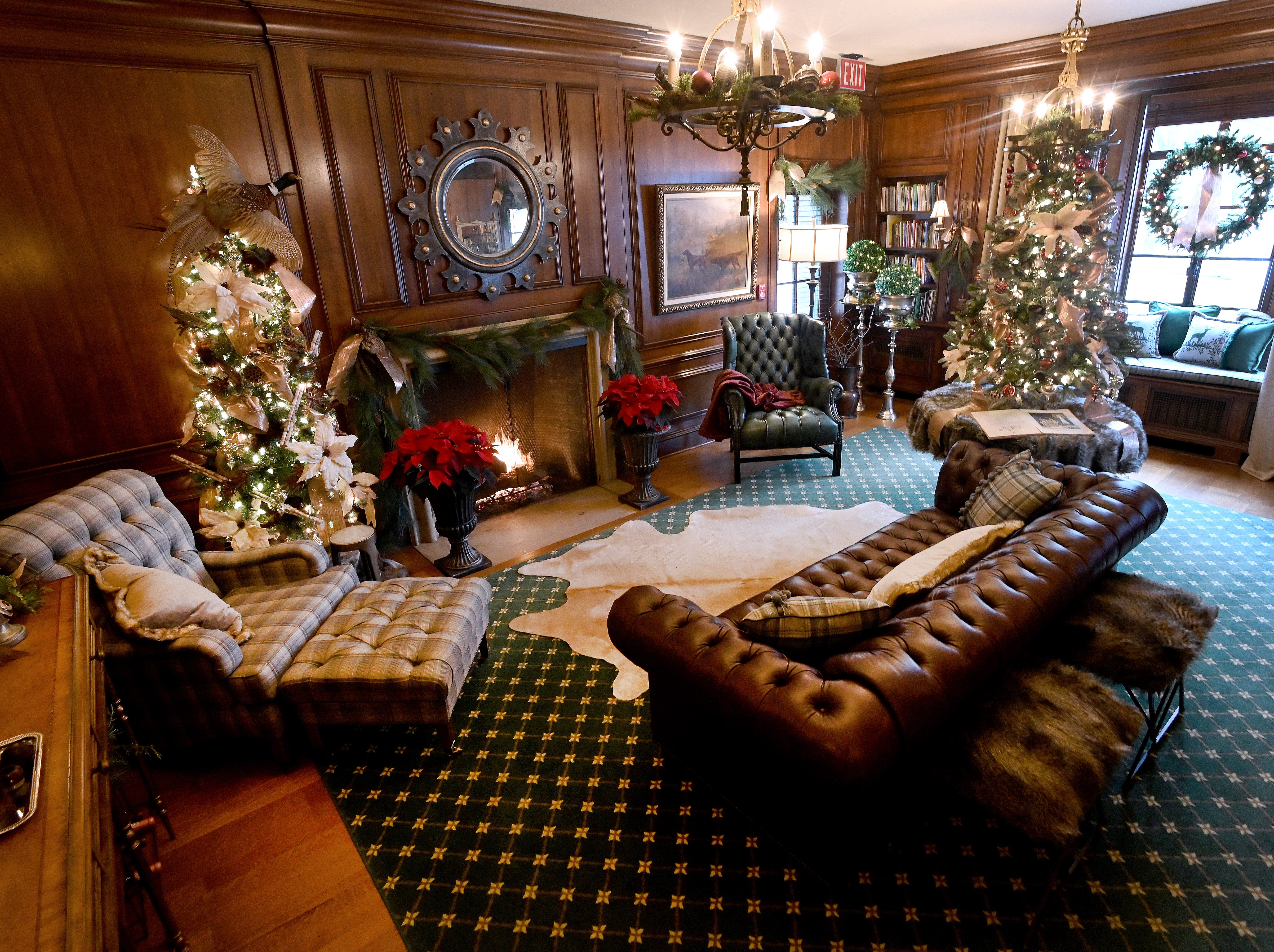 The manor's study is decked-out in Christmas finery, and a warm fire burns in the fireplace.