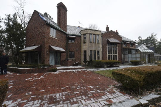 The rear of Aretha Franklin's former home is a mix of brick, masonry and glass, with a broad area of brick pavers.