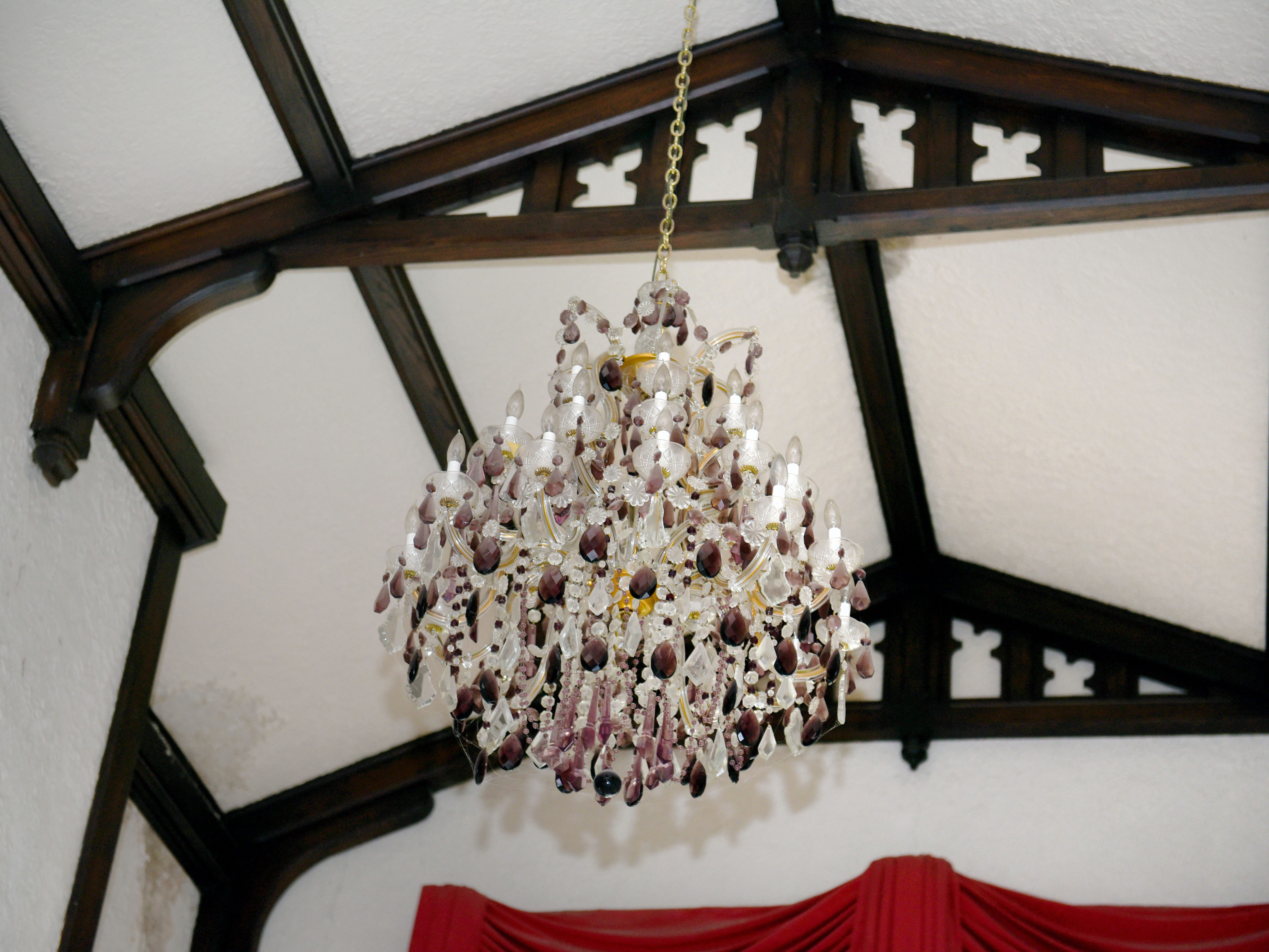 A chandelier dripping with crystals hangs from the ceiling in the main living space.