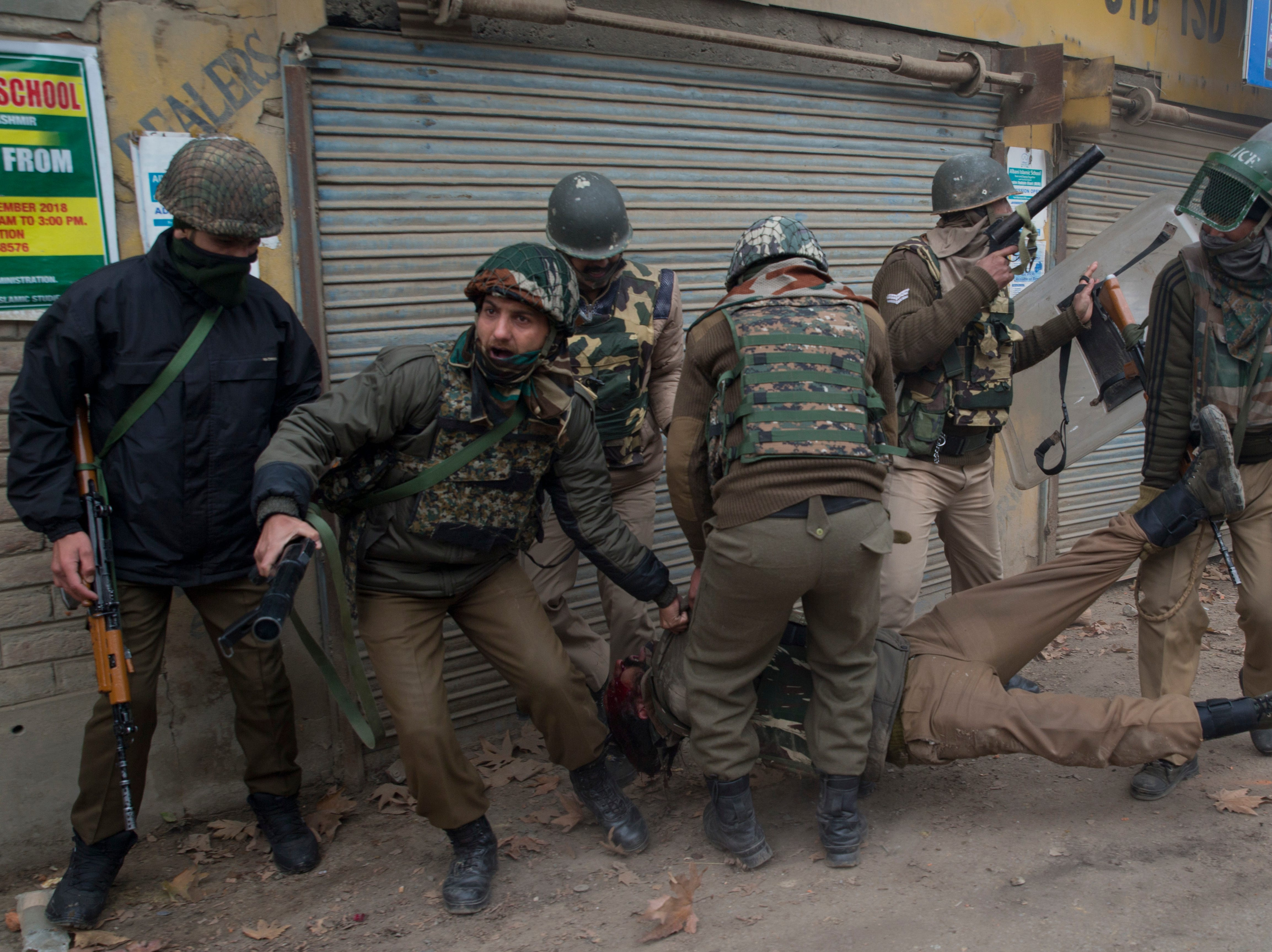 Indian paramilitary soldiers rush to help their colleague wounded during a clash with protesters near the site of  a gunfight in Badgam district, Indian-controlled Kashmir, Wednesday, Nov. 28, 2018. Police say they have killed an alleged Pakistani militant accused in the death of a prominent journalist.