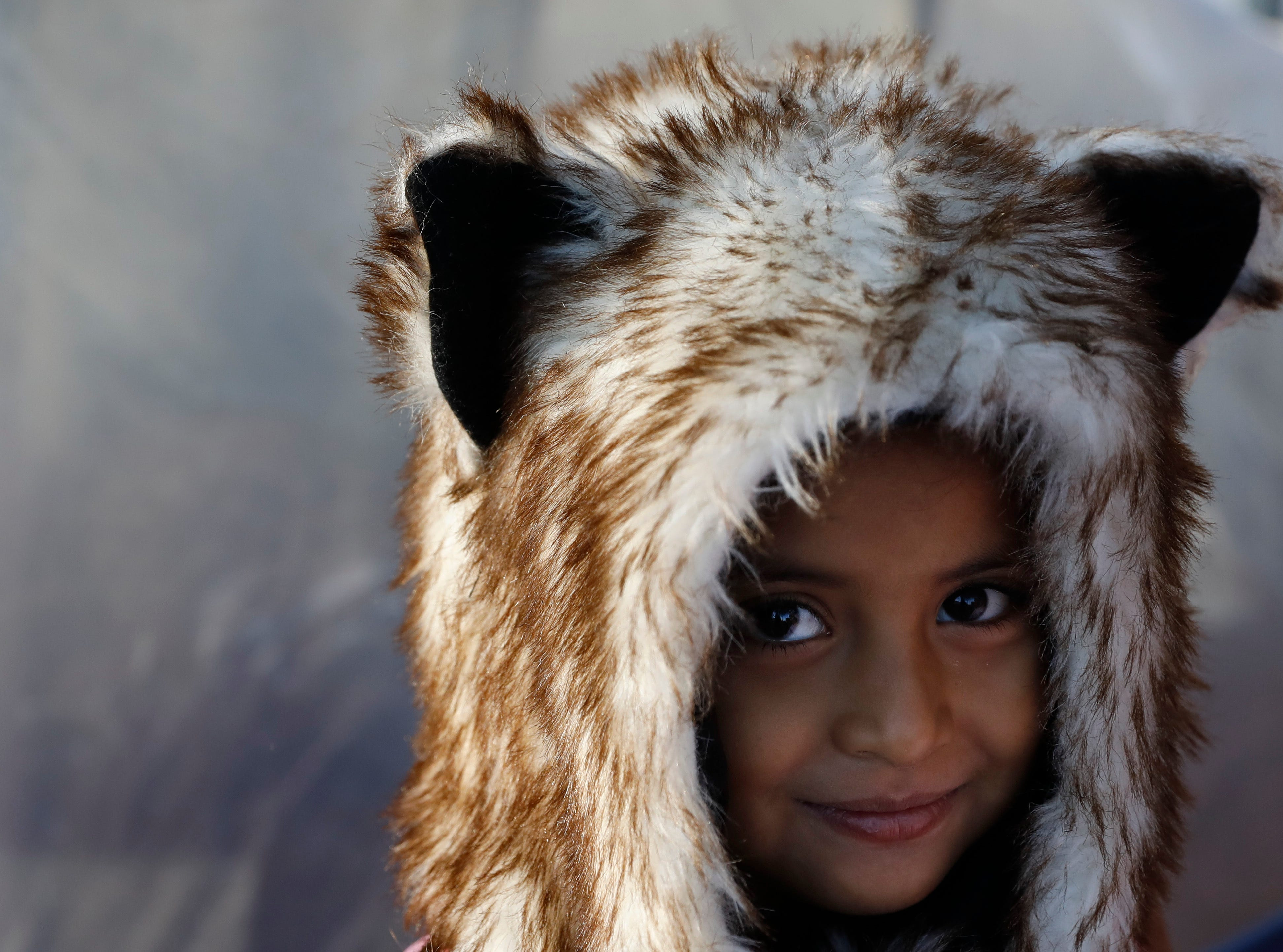 Honduran child migrant Gina keeps warm with a donated hood, outside the tent where her family of five is sleeping at an overflowing sports complex sheltering more than 5,000 Central American migrants, in Tijuana, Mexico, Wednesday, Nov. 28, 2018. As Mexico wrestles with what to do with the thousands of people camped out in the border city of Tijuana, President-elect Andres Manuel Lopez Obrador's government signaled Tuesday that it would be willing to house the migrants on Mexican soil while they apply for asylum in the United States, a key demand of U.S. President Donald Trump.