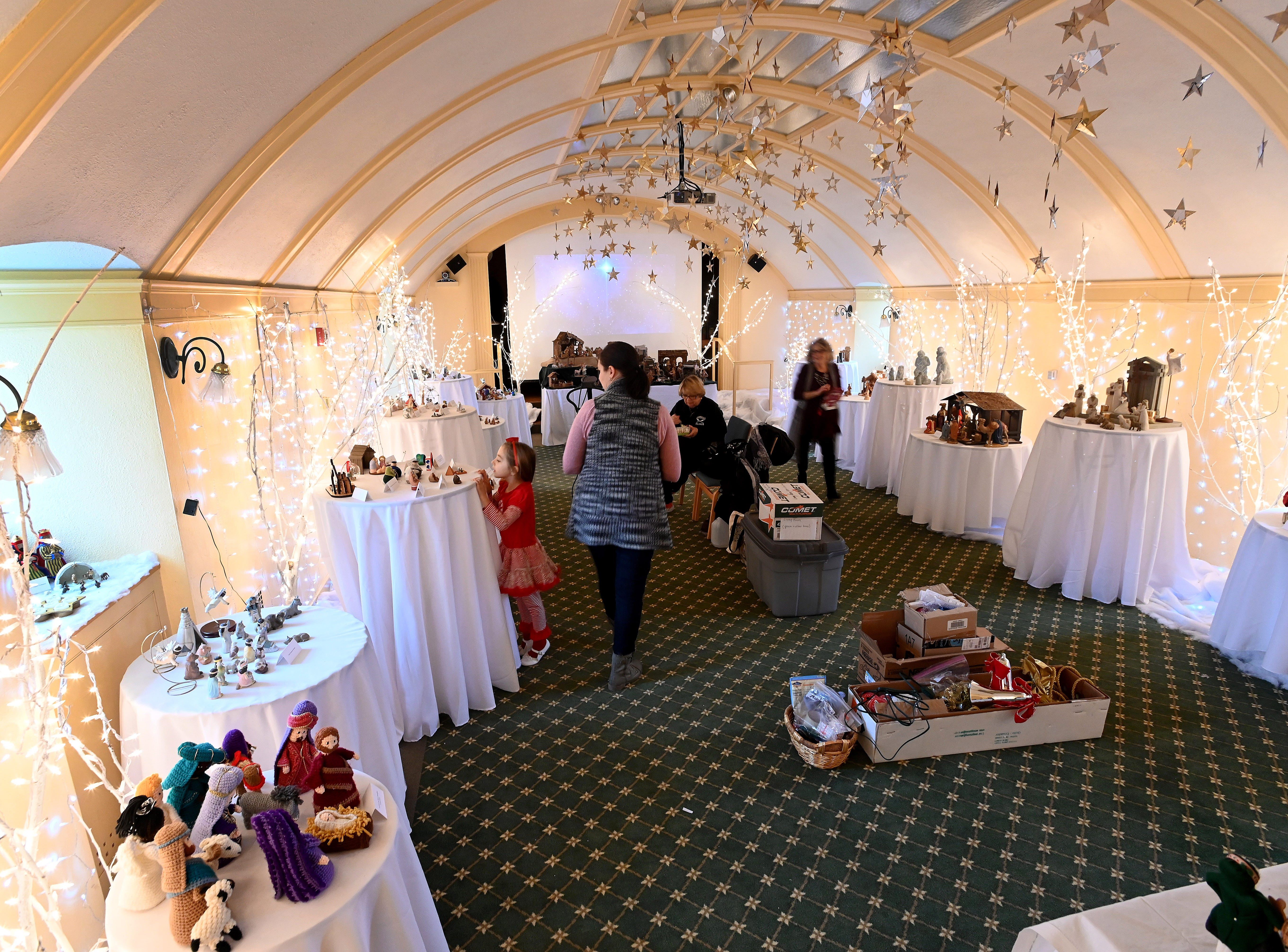 """Volunteers get to work decorating the """"Ballroom"""" in Earhart Manor with a collection of nativity scenes."""
