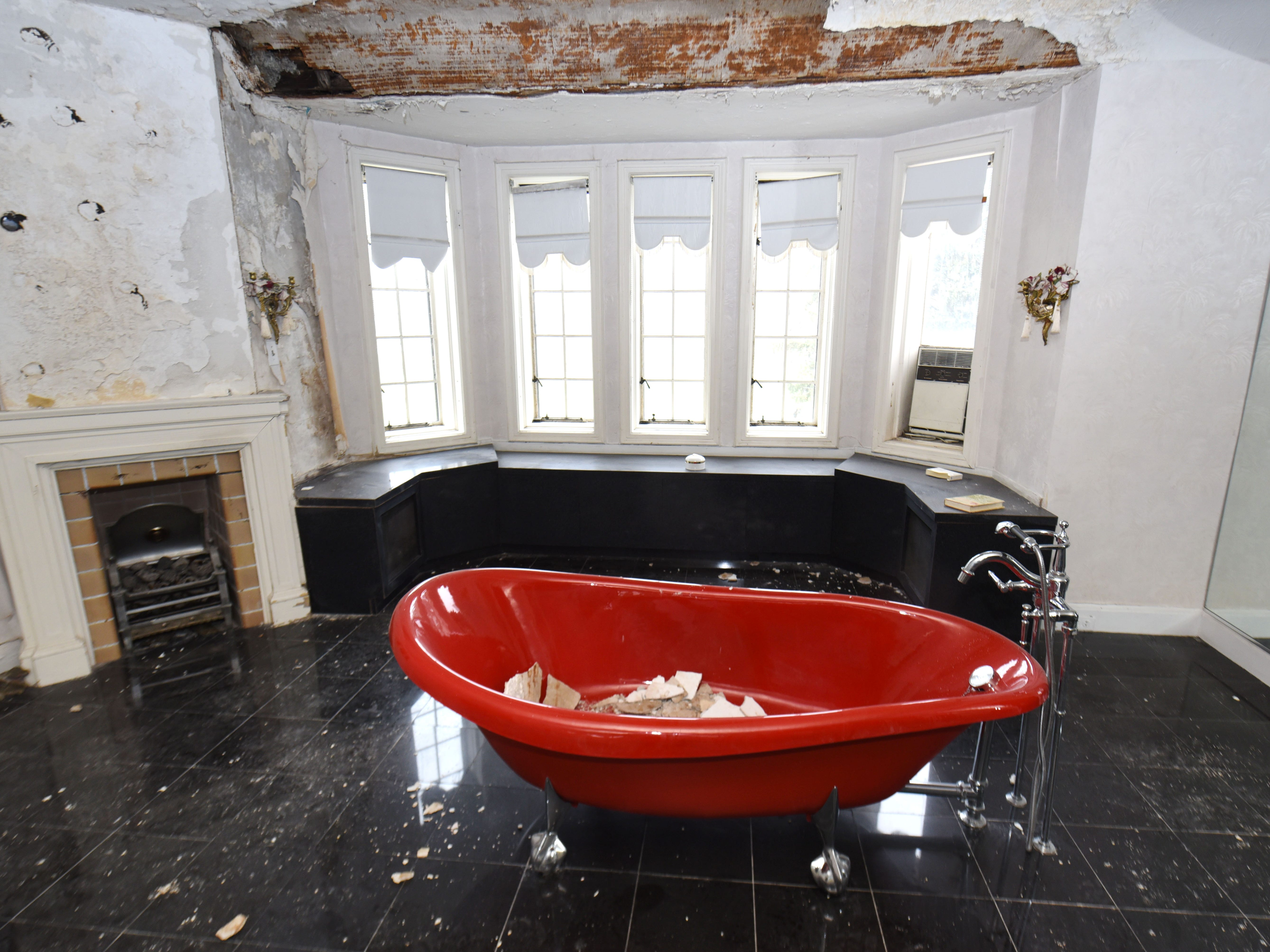 A bright red standing tub is the centerpiece of a grand bathroom at the former home of Aretha Franklin.