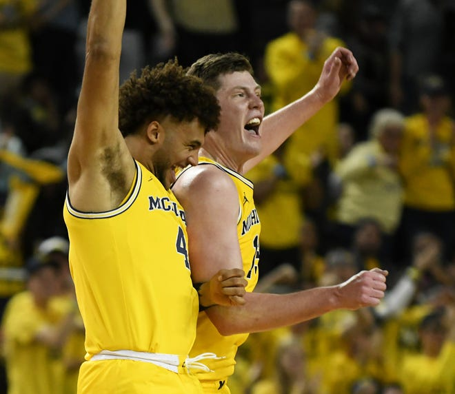 Michigan's Isaiah Livers (4) and Jon Teske (15) react at a time out after the lead for Michigan gets larger in the second half.