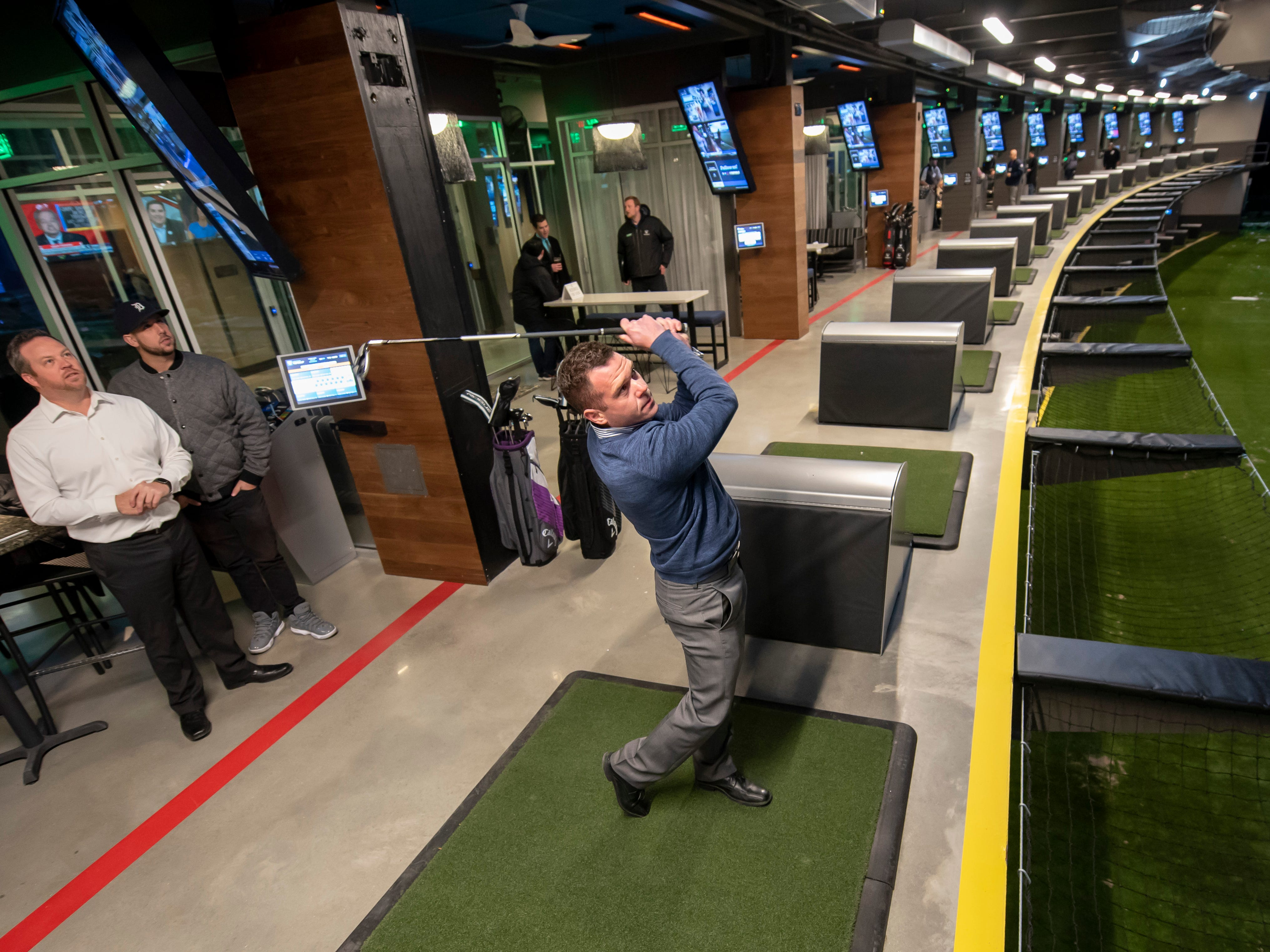 Brandon Bland, of Oxford, sends a ball into the driving range during a preview event at Topgolf, in Auburn Hills.
