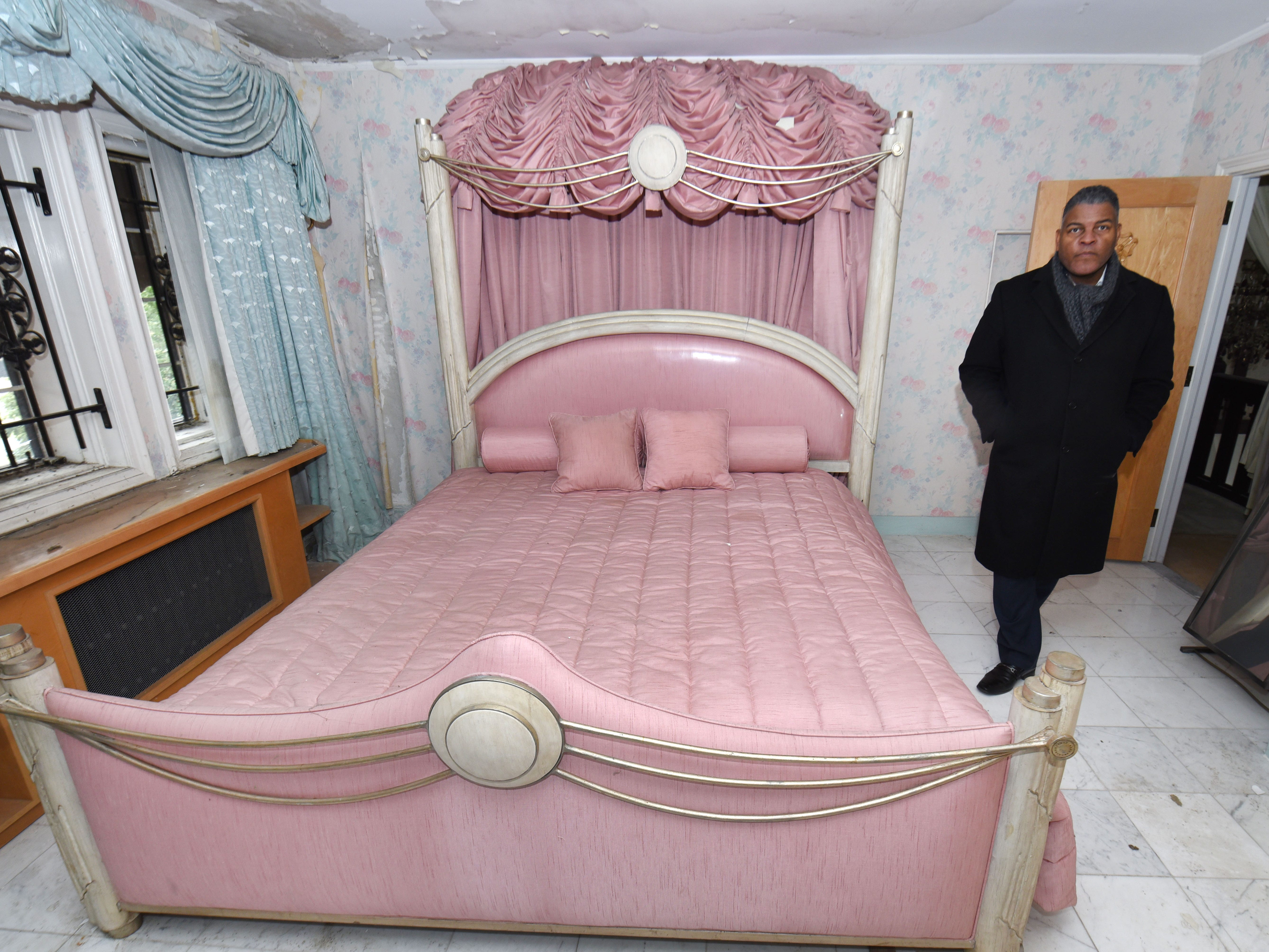 Anthony O. Kellum, president of Kellum Mortgage, stands in the former bedroom of Aretha Franklin, decorated in pink.