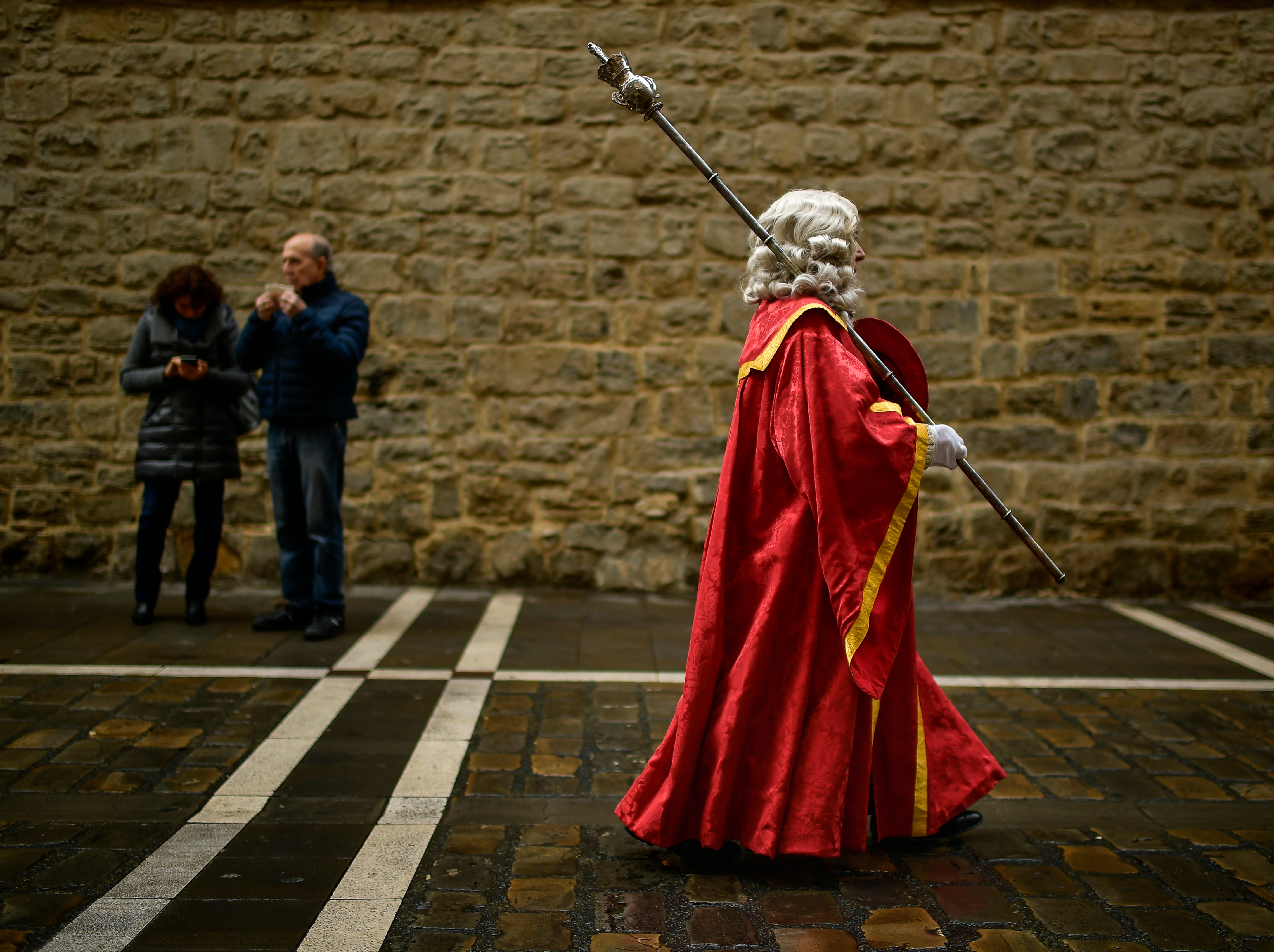 A man dressed in ancient regional costume walks along a street of the old city while taking part in a procession in honor of Saint Saturnino, in Pamplona, northern Spain, Thursday, Nov. 29 2018.