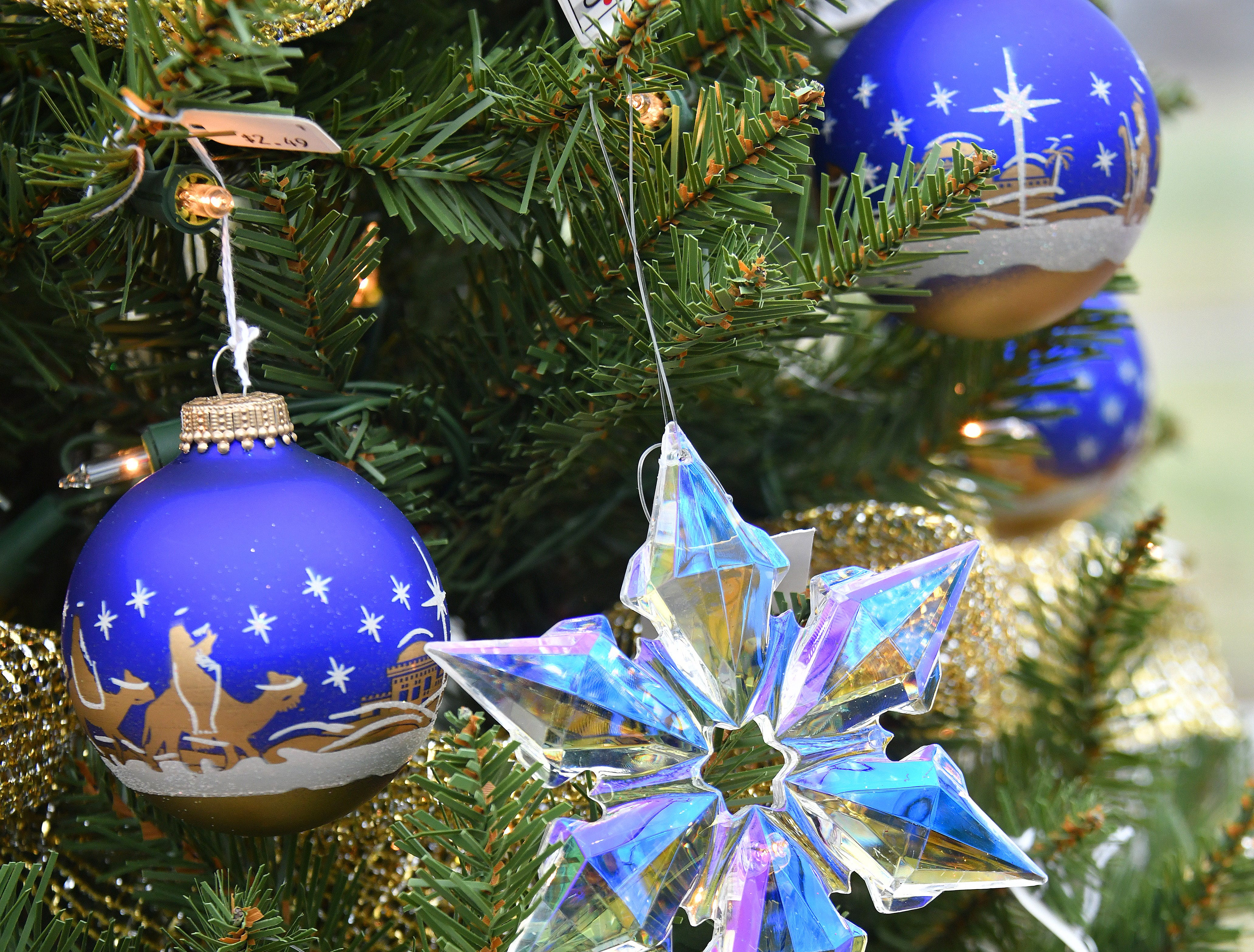 A decorated tree for sale in the greenhouse awaits a new home. The trees, with decorations from Bronner's in Frankenmuth, will be sold to raise money for charity.