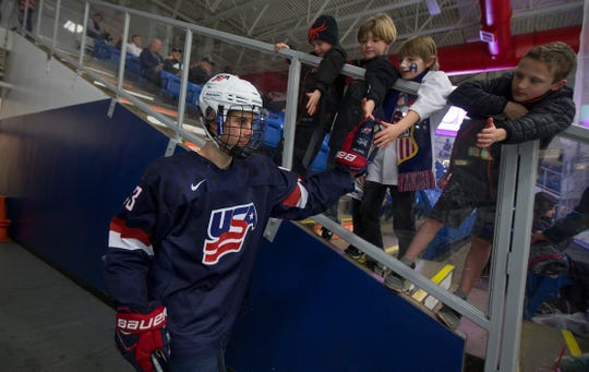 Jack Hughes touches the hands of young fans as he enters the rink at USA Hockey Arena in Plymouth.