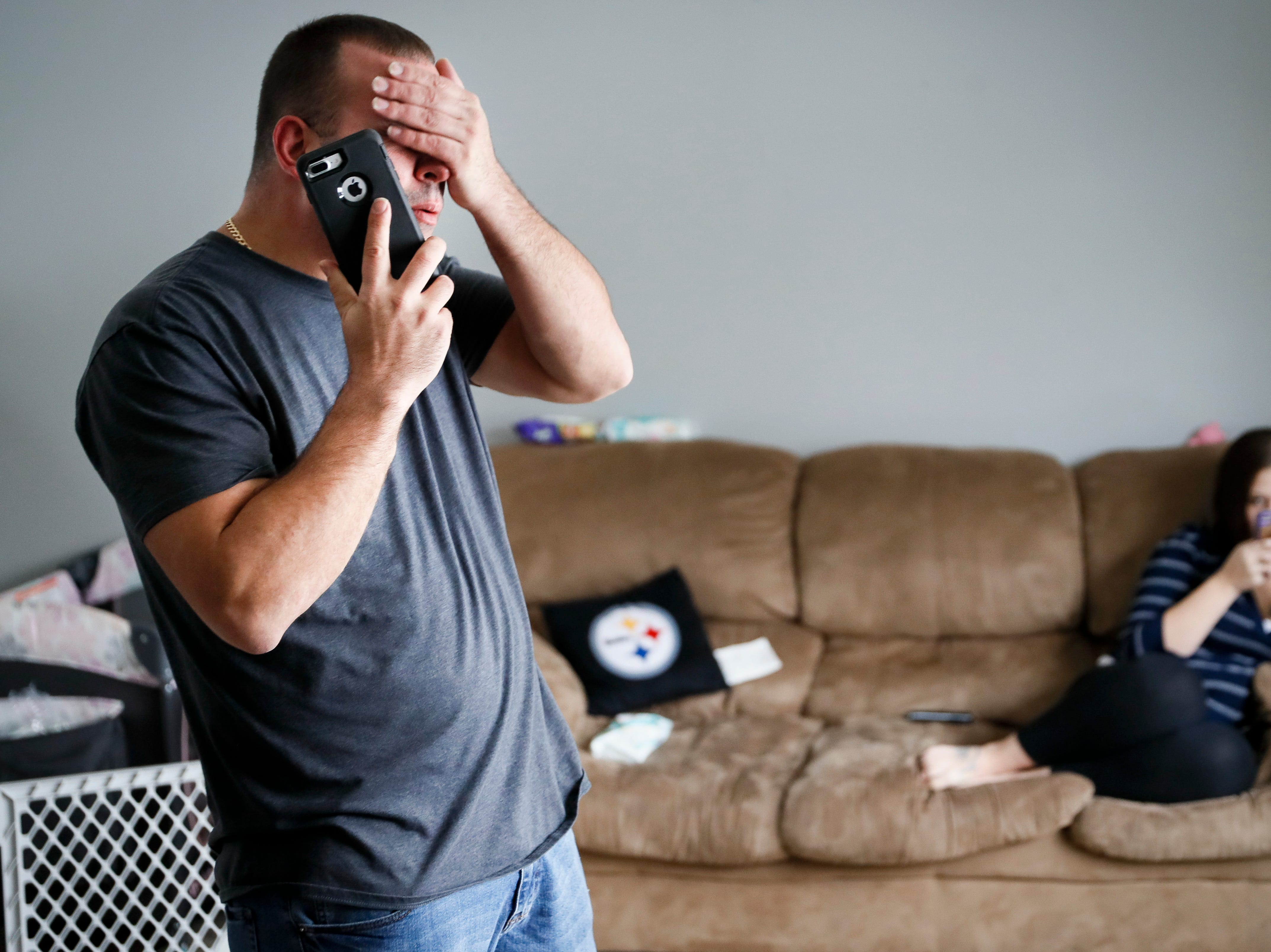 Tom Wolikow, a General Motors employee who is currently laid-off,  takes a phone call at home alongside his fiance Rochelle Carlisle, on Wednesday, Nov. 28, 2018, in Warren, Ohio. Though unemployment is low, the economy is growing and U.S. auto sales are near historic highs, GM is cutting thousands of jobs in a major restructuring aimed at generating cash to spend on innovation. GM put five plants up for possible closure, including the plant in Lordstown.