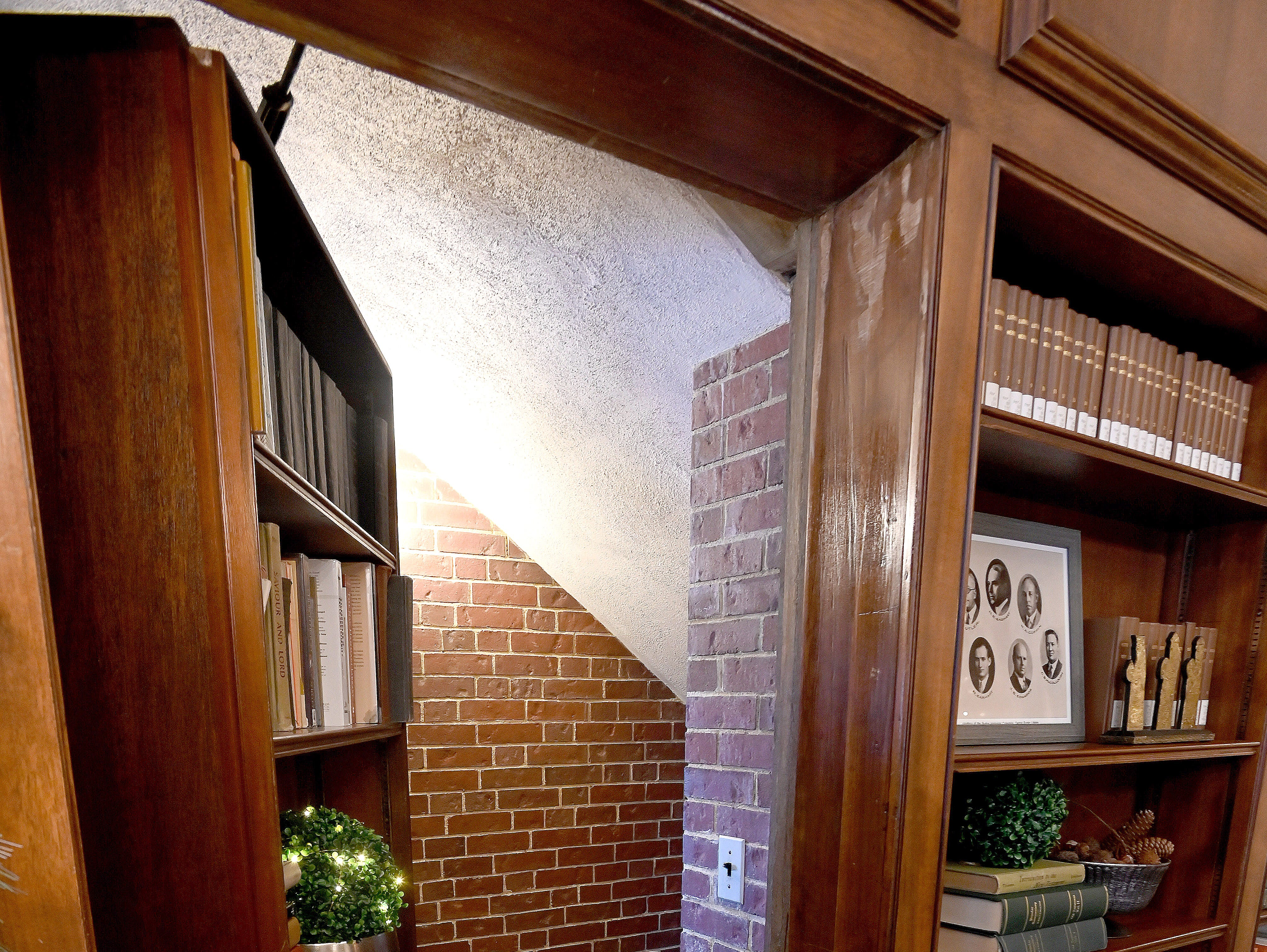 A hinged section of bookcase in the study hides a stairway to a hidden room below.