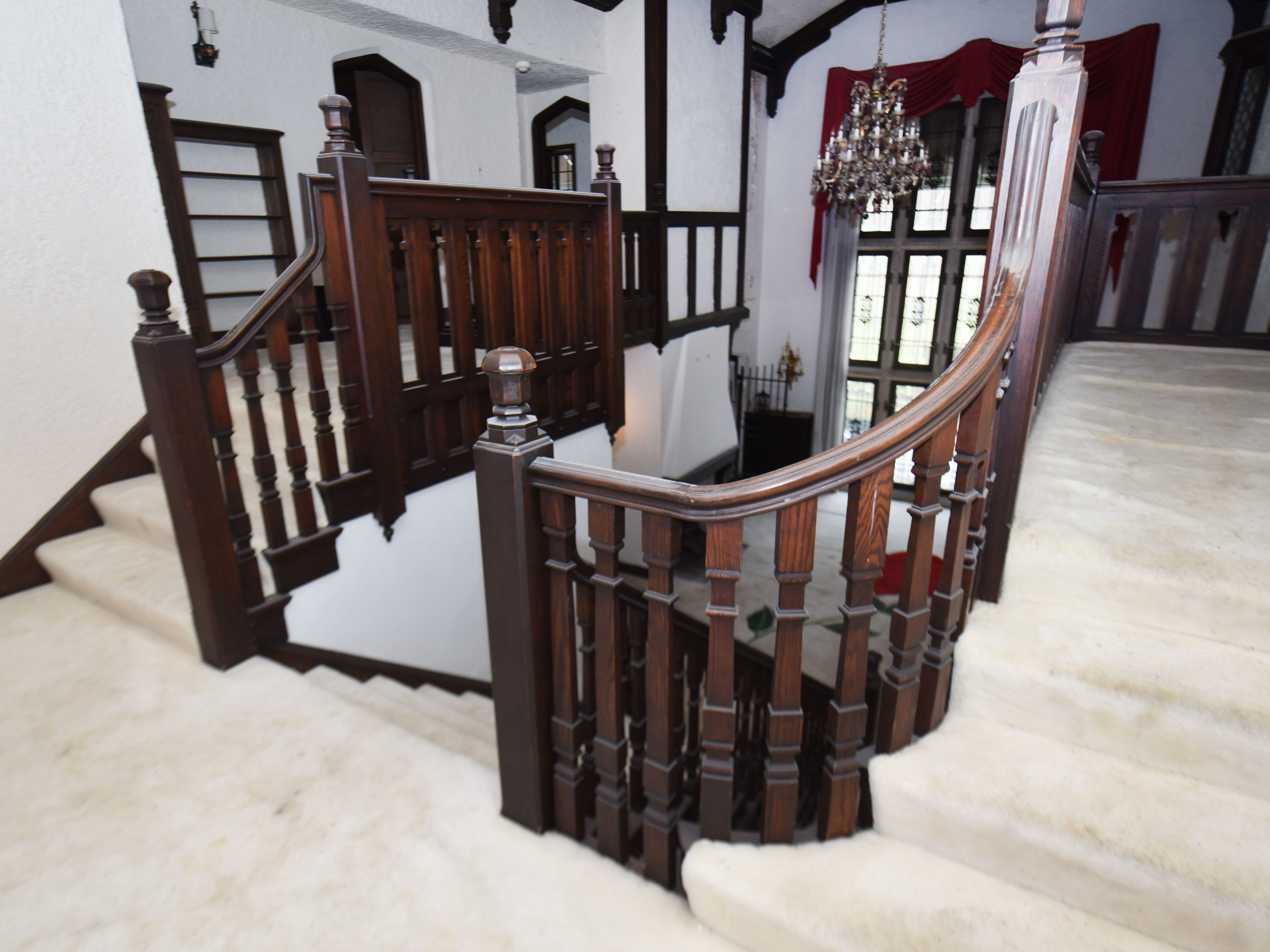 The carpeting extends to the second floor, which has a curved balustrade.