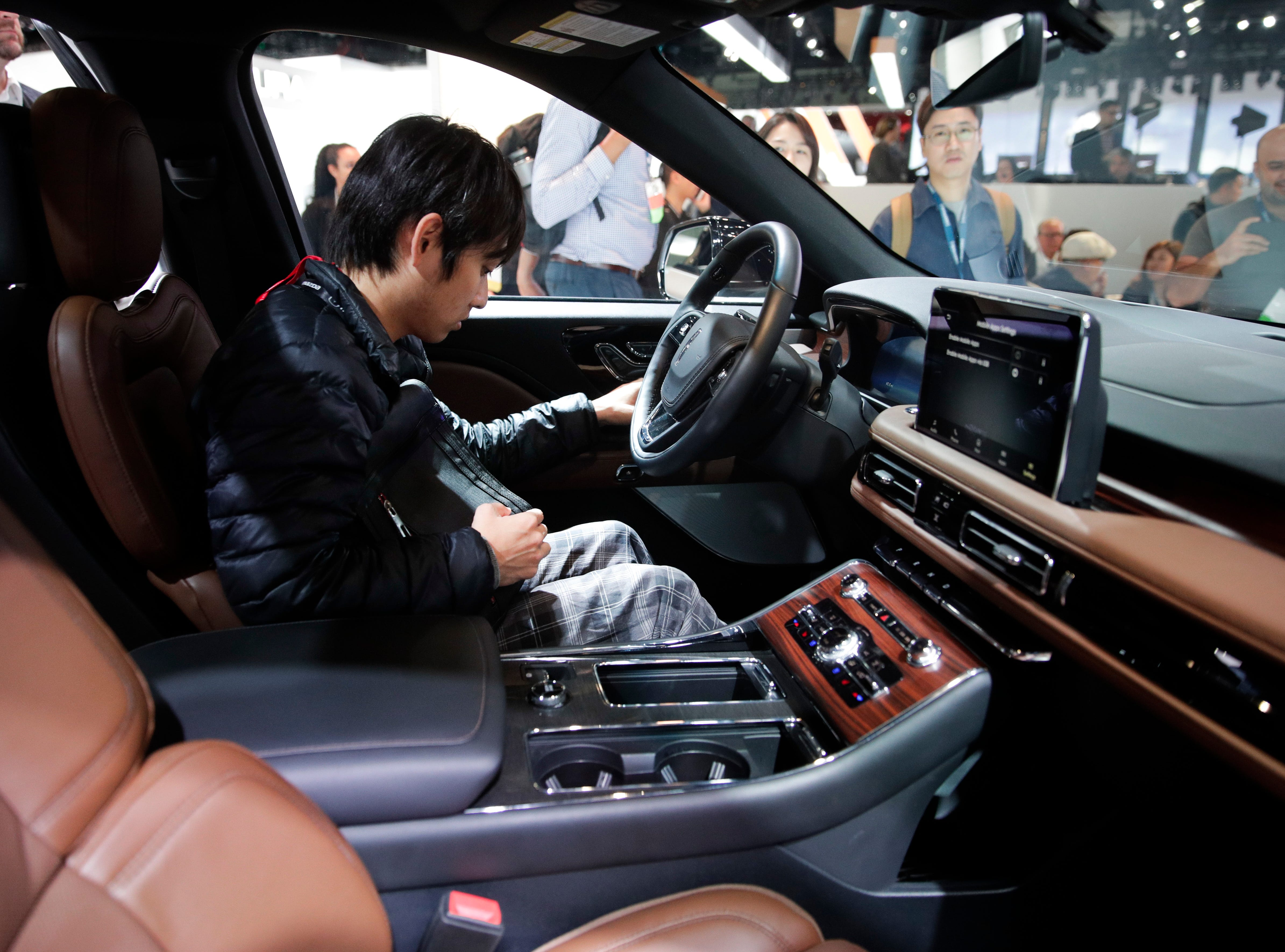 An attendee sits in the 2020 Lincoln Aviator at the Los Angeles Auto Show Wednesday, Nov. 28, 2018, in Los Angeles.